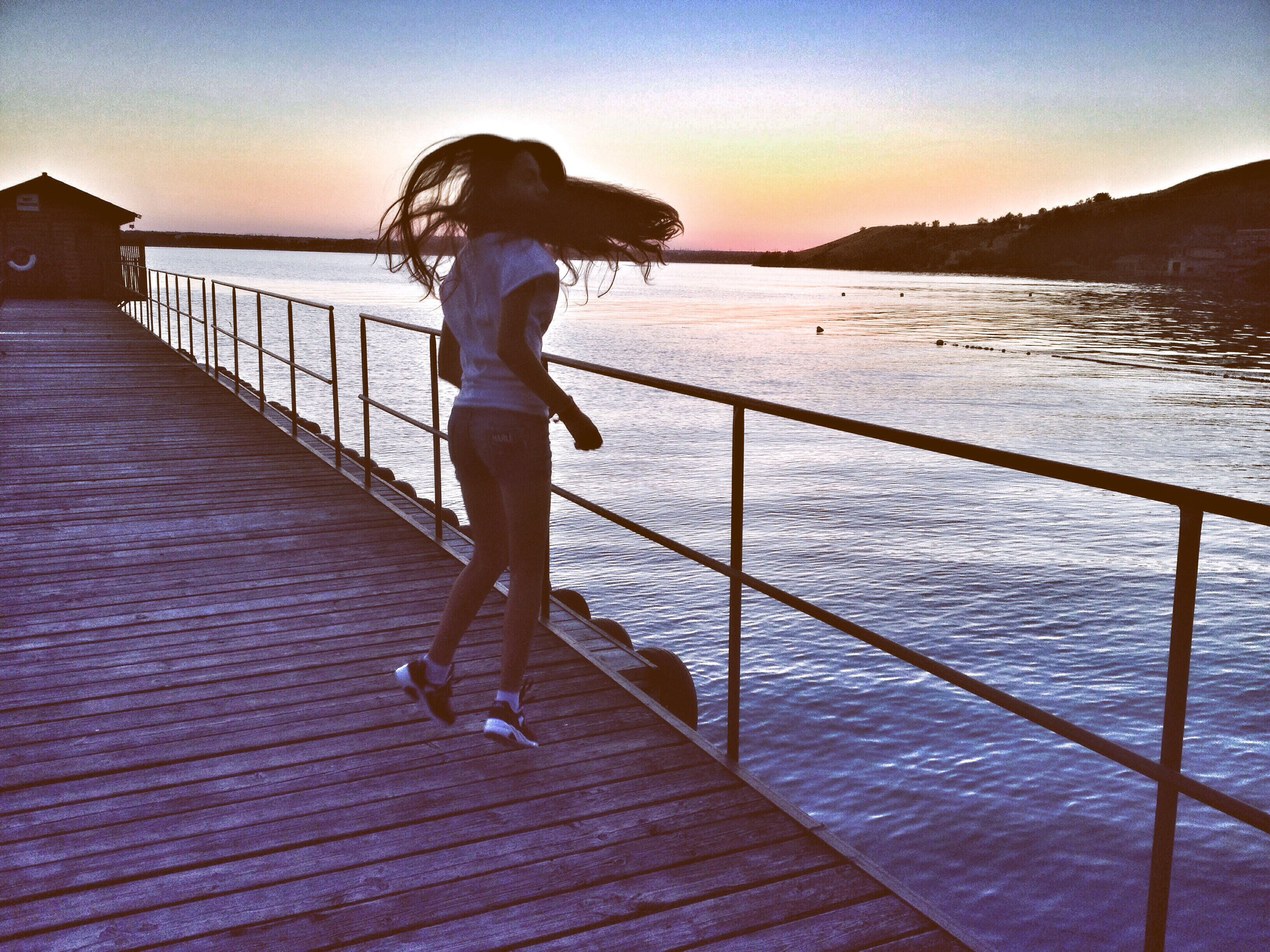 railing, full length, water, sea, sky, sunset, outdoors, pier, rear view, one person, horizon over water, vacations, standing, nature, leisure activity, people, adults only, adult, beauty in nature, beach, bridge - man made structure, one woman only, day, only women