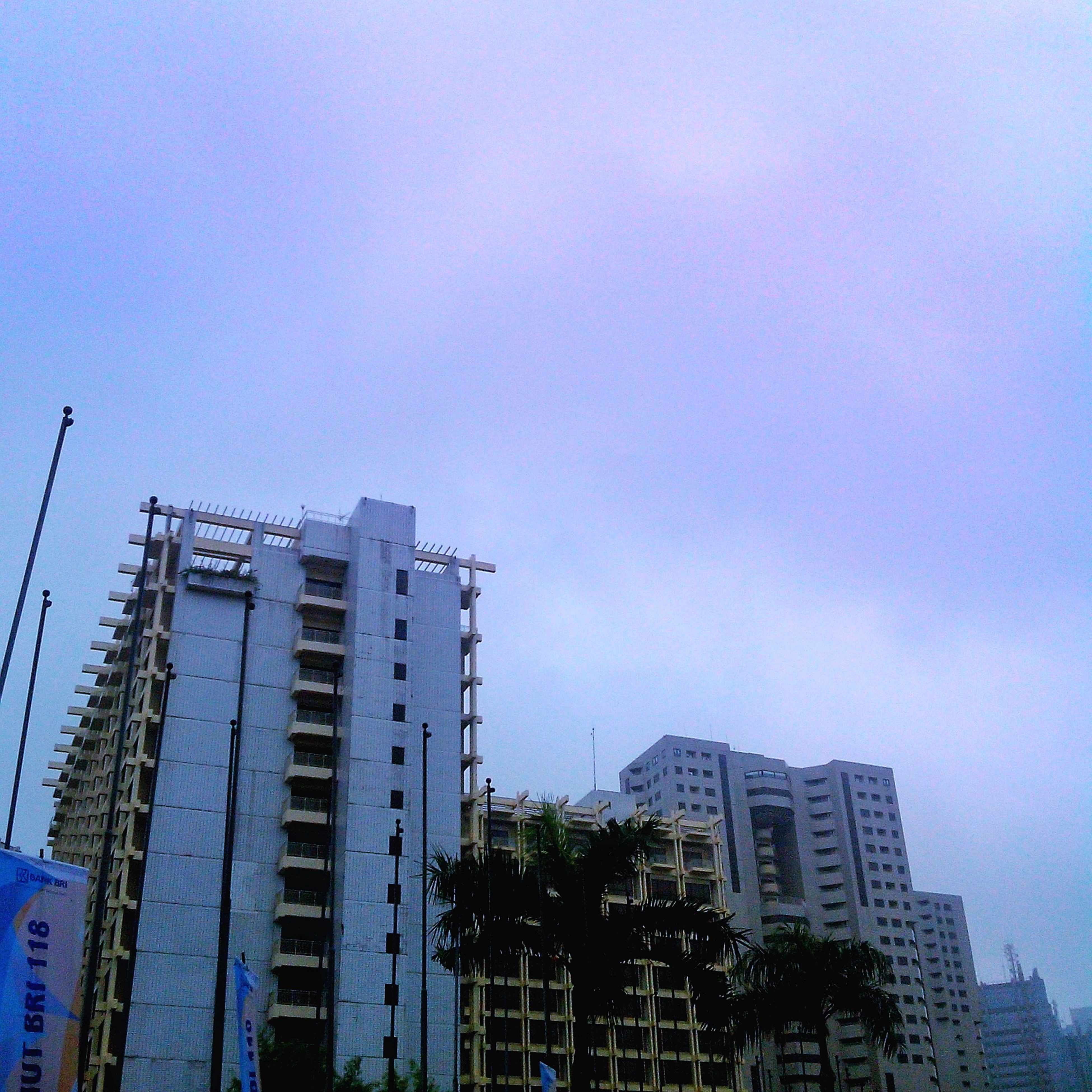 building exterior, architecture, built structure, city, low angle view, building, development, clear sky, copy space, sky, residential building, skyscraper, residential structure, tall - high, crane - construction machinery, tower, office building, outdoors, modern, day