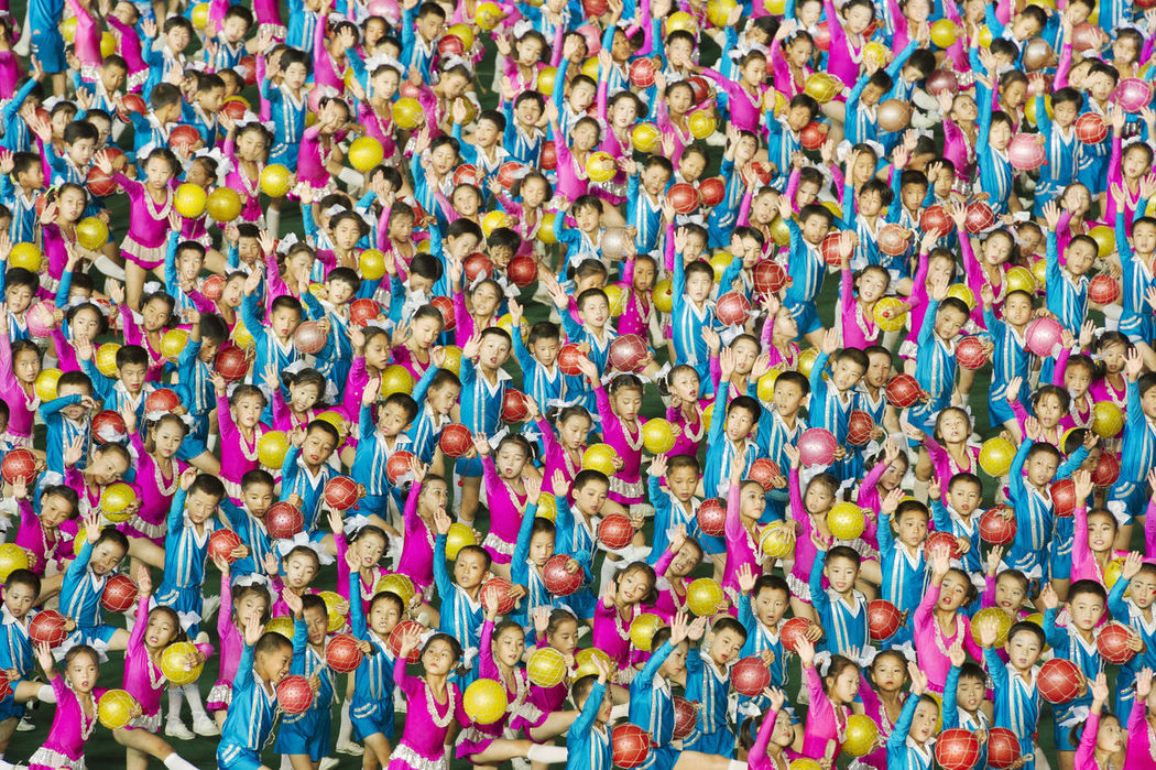 Arirang Mass Games at Mayday Stadium in Pyongyang, North Korea, a 120,000 performer-strong spectacle of gymnastic choreography in one of the biggest sport arenas in the world. At the stand behind the field 30,000 person flip card mosaic to form detailed composite pictures.The performance takes place for two months in August and September. From as young as 5 years old kids are being selected to participate in the Mass Games. Arirang Backgrounds Colorful Colors Dance Dictatorship DPRK Festival Front View Full Frame In A Row Kids Mass Games Multi Colored North Korea Performance Traditional Beautifully Organized