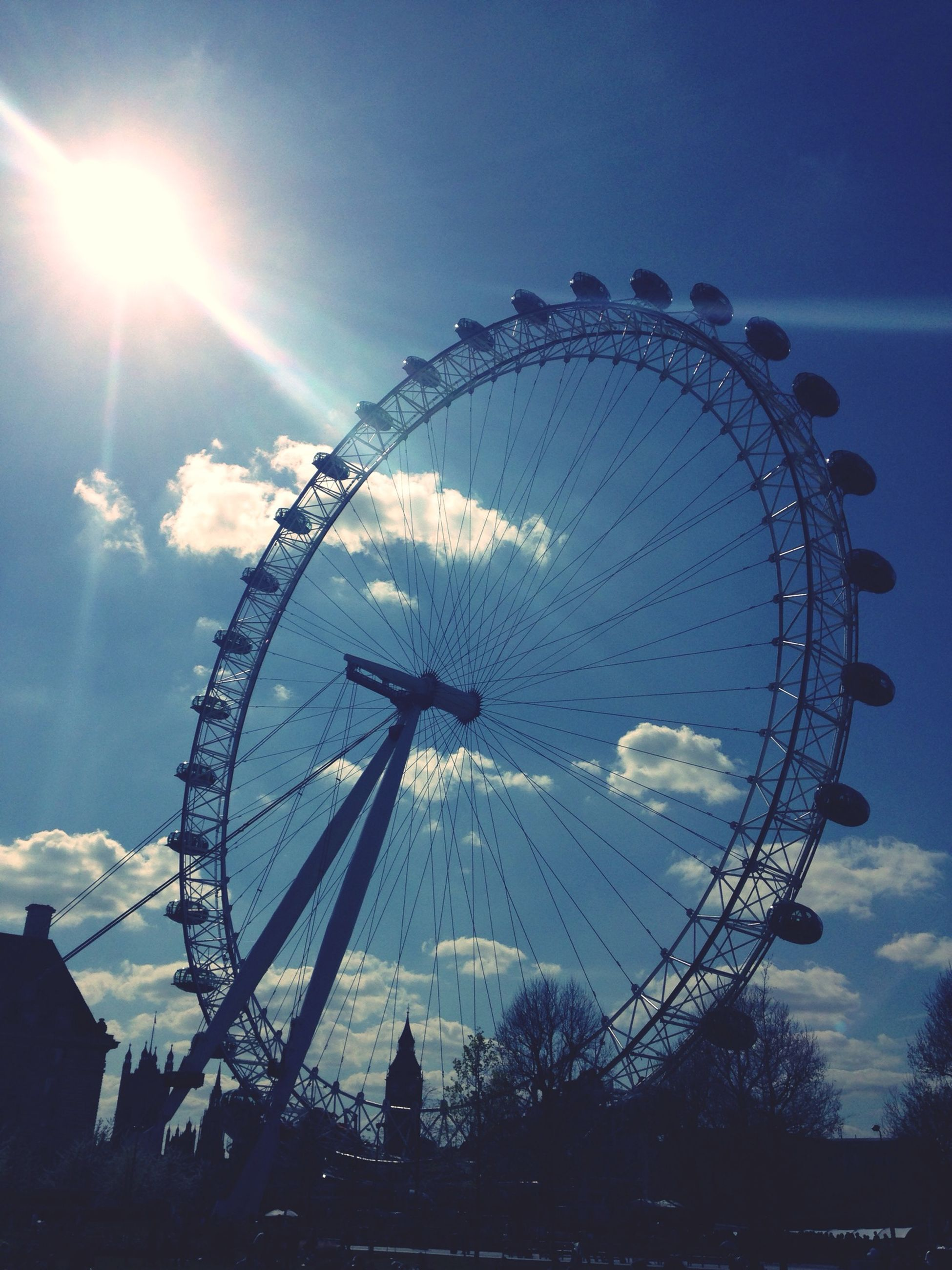 ferris wheel, amusement park ride, amusement park, arts culture and entertainment, sky, low angle view, sun, built structure, architecture, silhouette, cloud - sky, circle, travel destinations, tourism, fun, famous place, travel, sunlight, outdoors, cloud