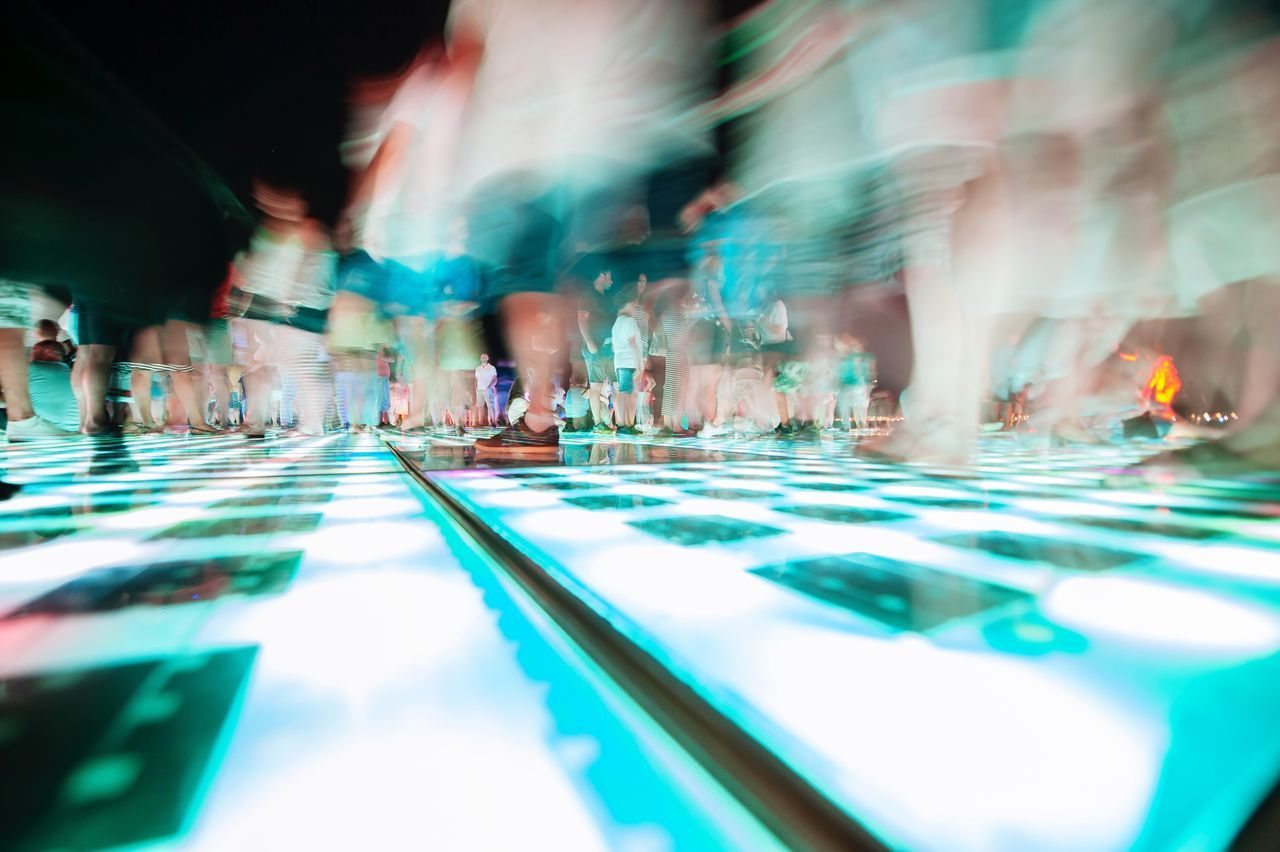 Blurred Motion Of People On Illuminated Dance Floor