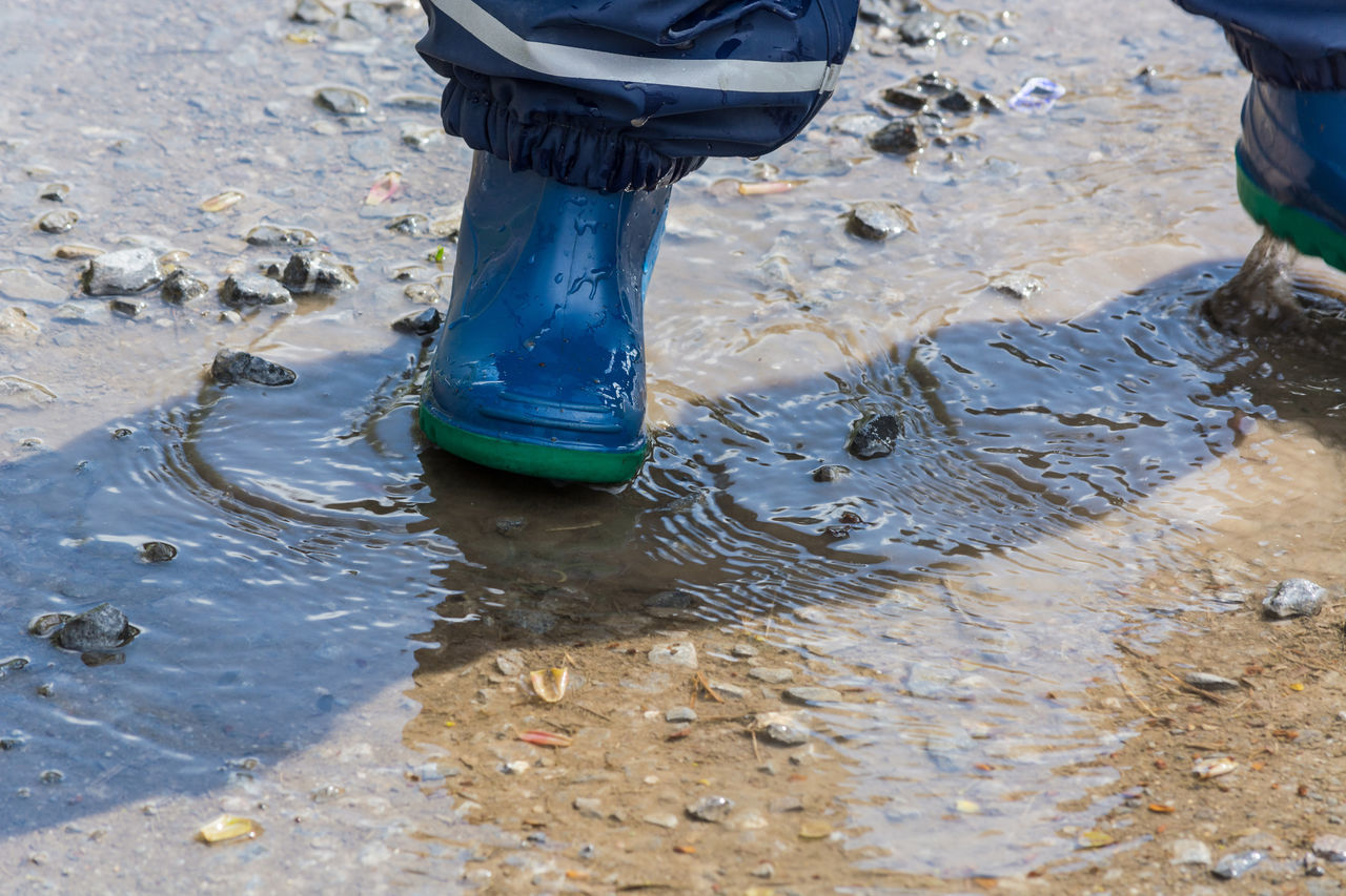 Child with blue rubber boots in a puddle. close up view Adult Adults Only Boots Dance Day Drops Human Body Part Human Leg Lifestyles Low Section Men Occupation One Person Outdoors People Puddle Real People Relaxing Rubber Boots Tanggy Water Winter