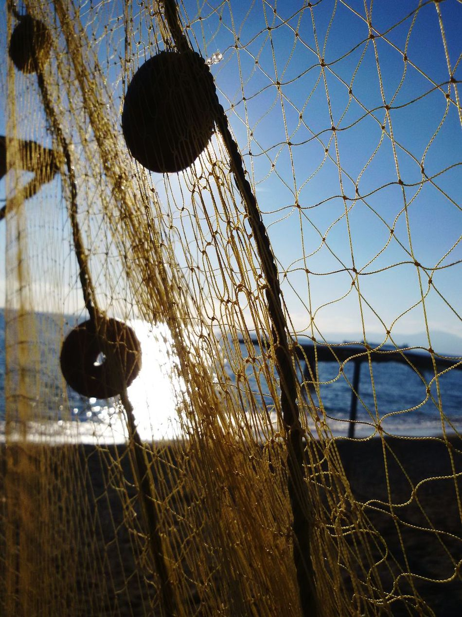 December in greece! Greece Kalamata Sunlight Sky Low Angle View Close-up Day Sea Fishnet Fishnets Hanging Outdoors Water Beach Sun Traditional Fishing Fishing Net Fishing Nets