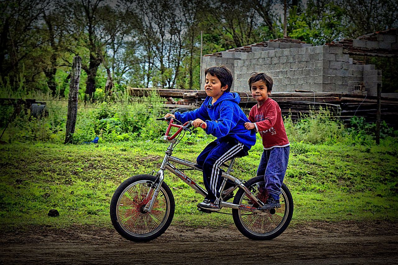 Two young children on a bicycle on a dirt road