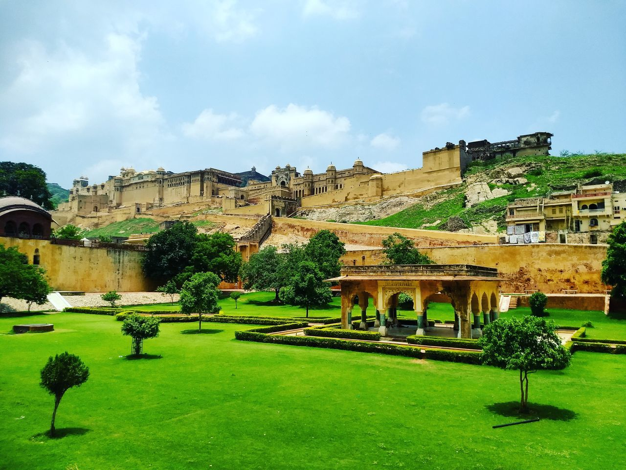architecture, built structure, building exterior, sky, history, grass, day, tree, outdoors, green color, travel destinations, cloud - sky, no people, nature, ancient civilization