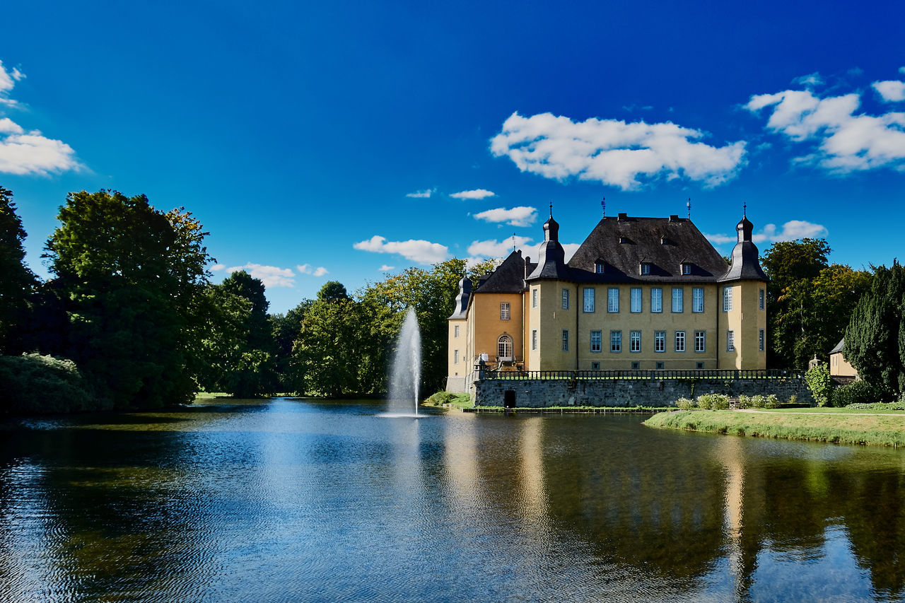 Juechen, Germany - September 27, 2015: View on famous castle of Juechen during warm and sunny weather with a blue sky. Architecture Architecture Blue Blue Sky Built Structure Castle Of Dyck Cloud - Sky Green Color Grmany Historic History Jüchen Lake Love No People Park Politics And Government Reflection Schloss Dyck Sky Tradition Travel Travel Destinations Tree Water