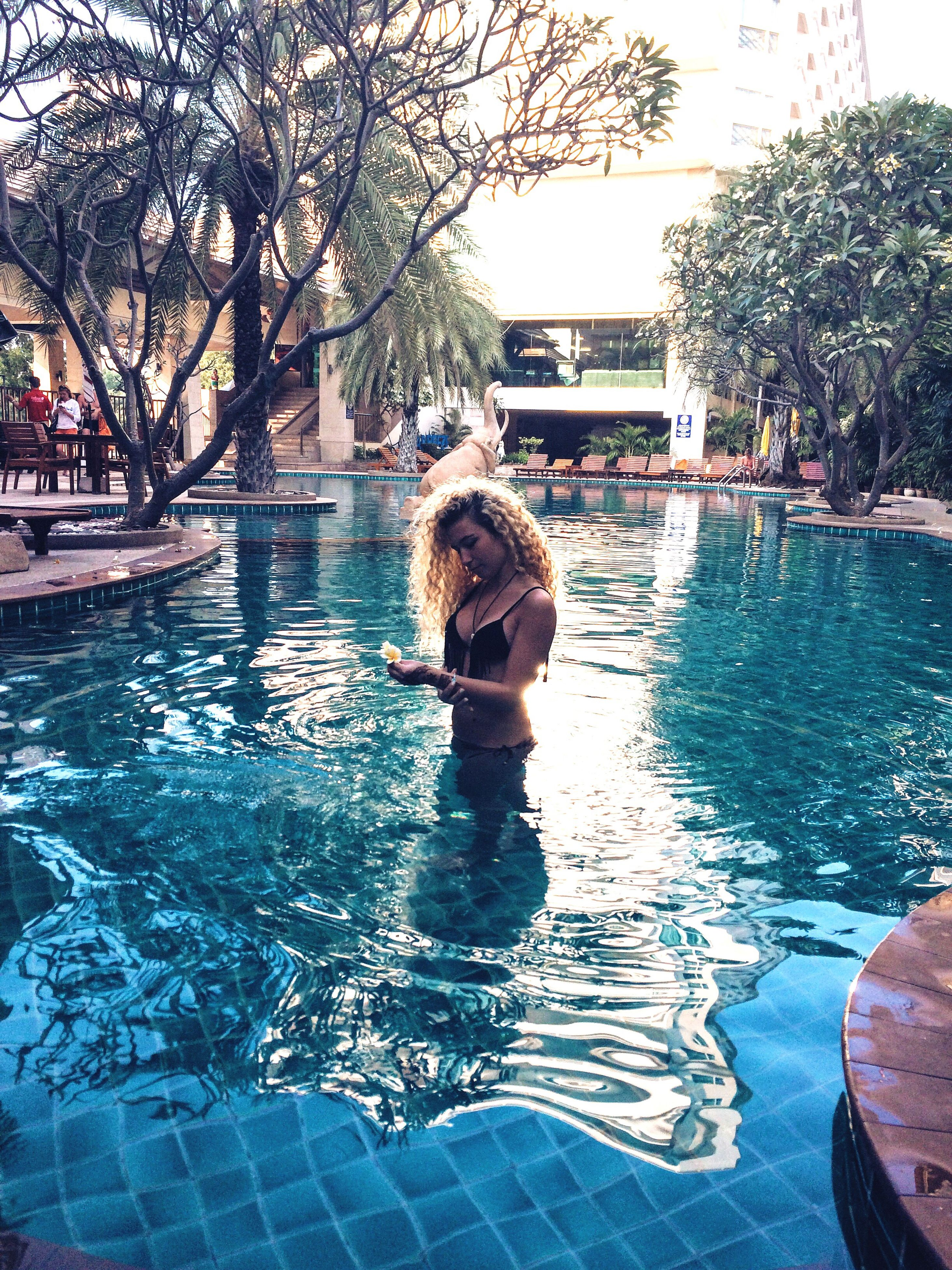 water, tree, lifestyles, built structure, leisure activity, building exterior, architecture, full length, swimming pool, reflection, rear view, day, childhood, outdoors, casual clothing, river, standing, swimming