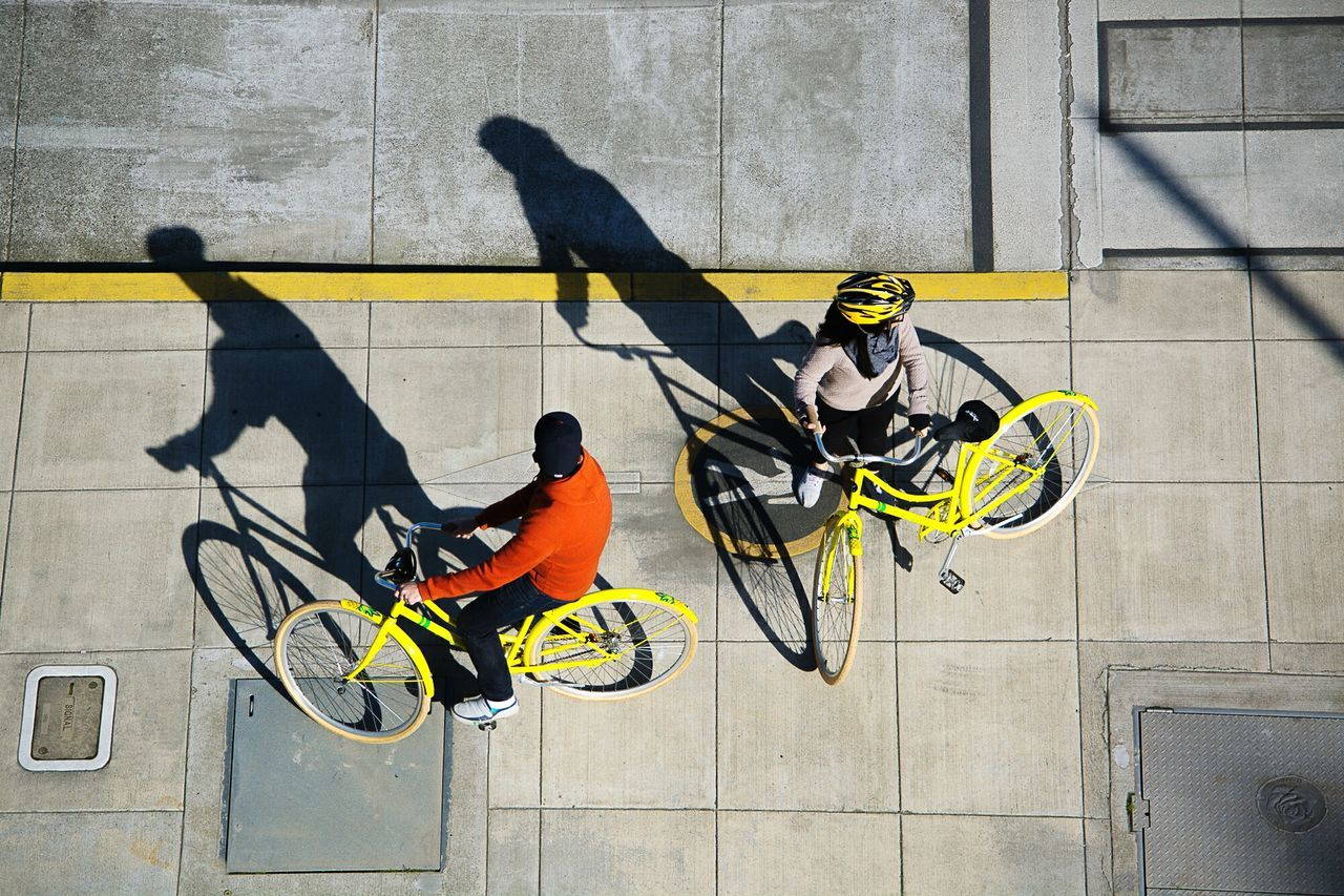 High Angle View Of Friends With Bicycle On Footpath