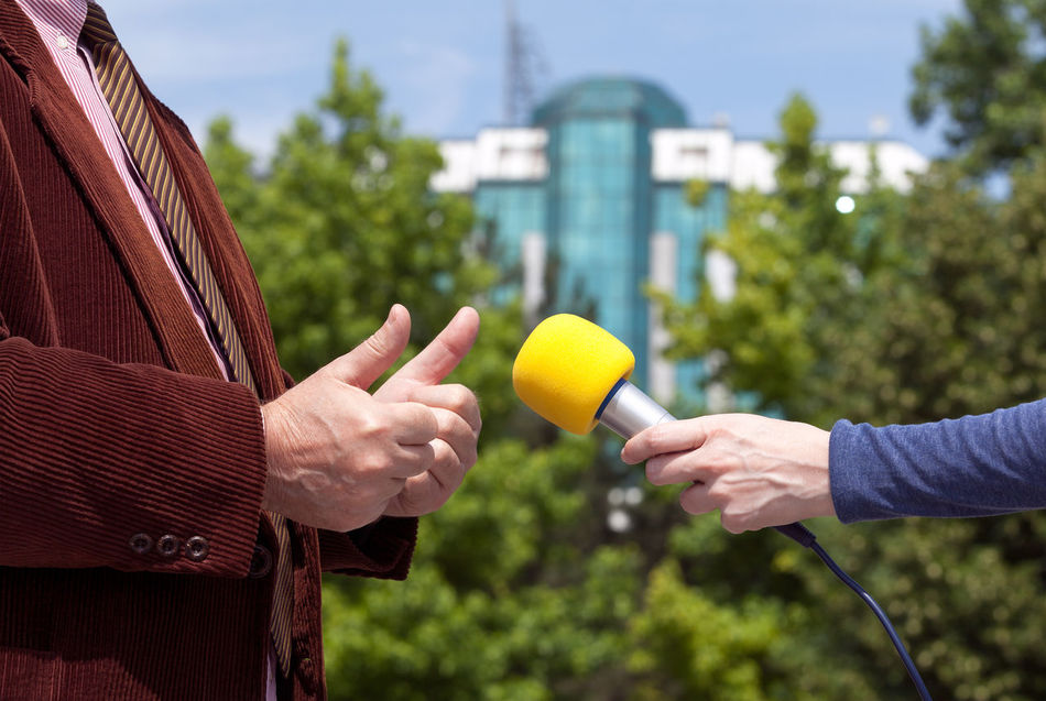 Journalist making media interview with businessman Adult Broadcasting Businessman City Close-up Day Human Hand Interview Leisure Activity Men Microphone Stand Outdoors People Politics Press Question Radio Sky Suit Taking Photos Two People