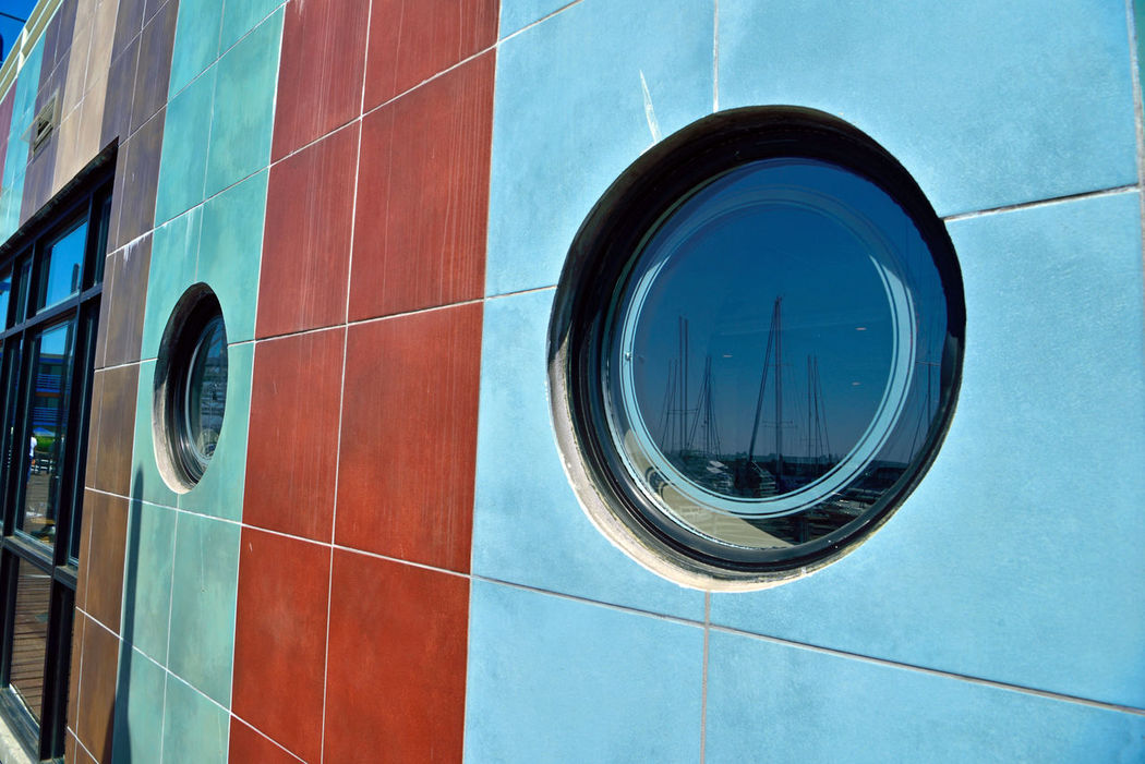 Oculi @ Jack London Square 5 Oakland, Ca. Oculus Round Windows Stone Tiled Facade Reflection Reflections In The Glass Windows Colorful Tiles Circles Squares Sailboat Masts Masts Windows Sky Marina Reflected Glory Glass Architecture Architectural Detail Architectural Feature Architecture_collection Reflection_collection Geometric Shape
