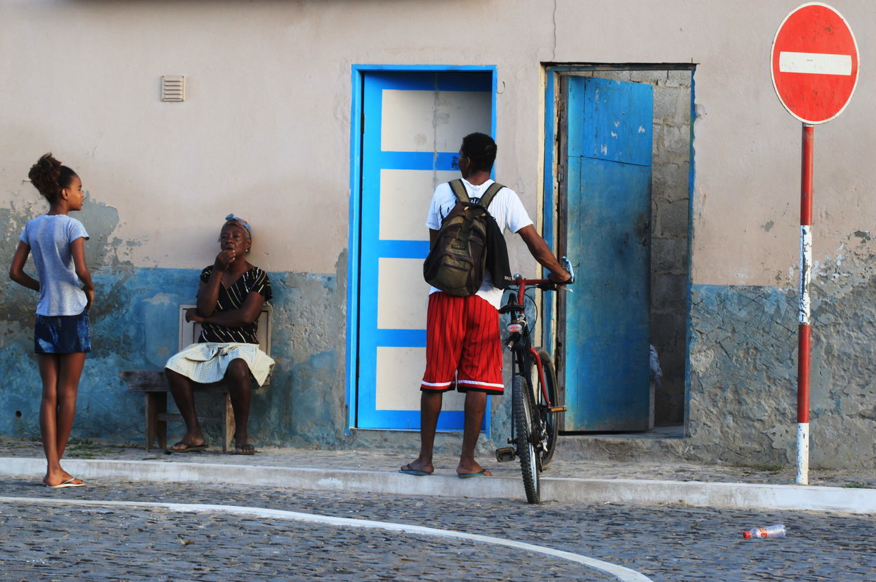 Architecture Boy Building Exterior Built Structure Capo Verde City Day Full Length Girl Old Woman Outdoors Real People Road Sign Sal Island Santa Maria Sitting Outside Summer 2015 The Street Photographer - 2017 EyeEm Awards