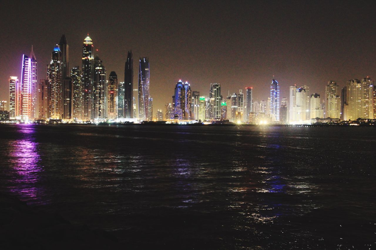 building exterior, architecture, night, built structure, illuminated, skyscraper, waterfront, water, modern, cityscape, travel destinations, no people, city, sea, urban skyline, outdoors, sky