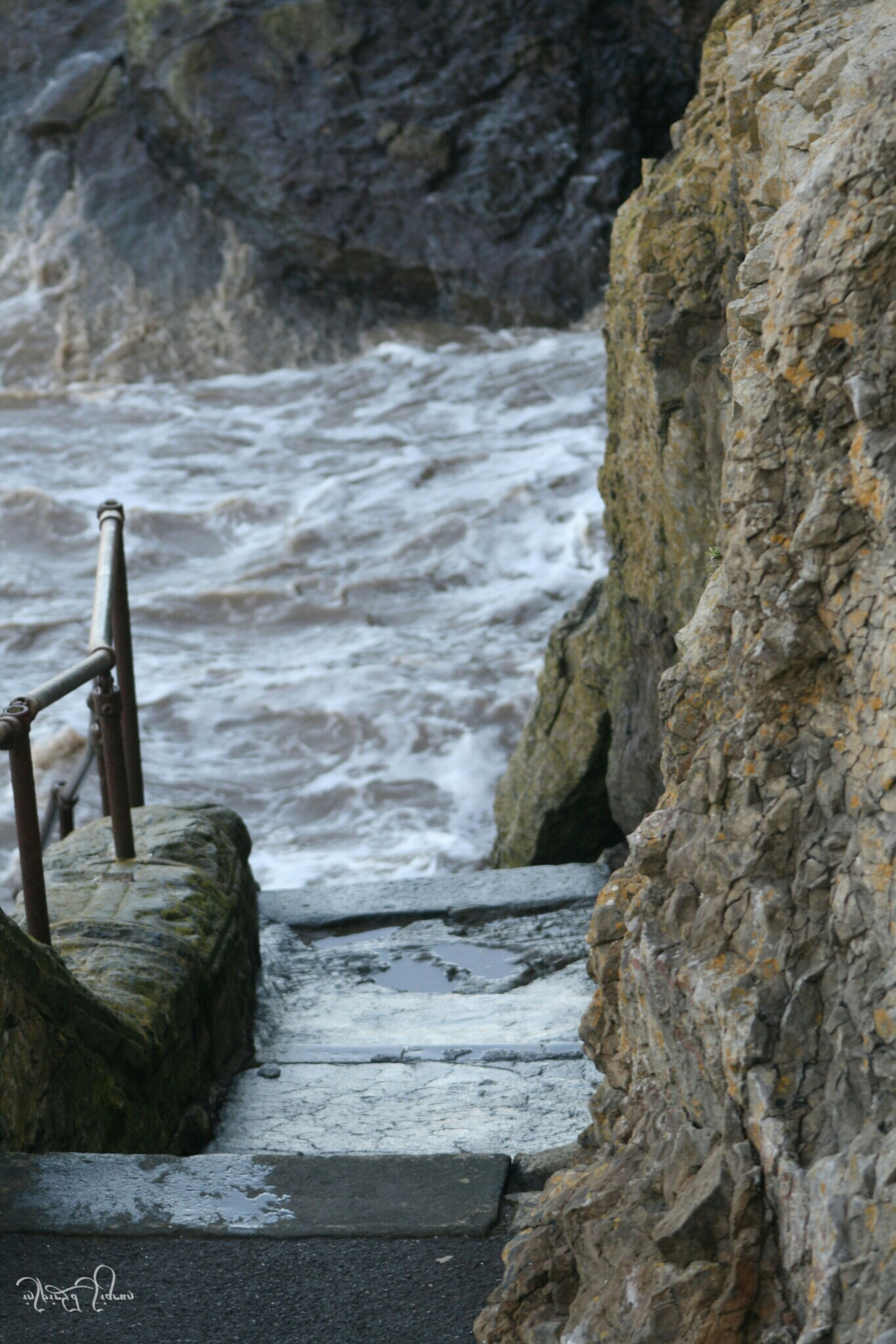 water, sea, rock - object, railing, wood - material, nature, day, tranquility, outdoors, no people, beauty in nature, pier, wave, high angle view, scenics, rock formation, close-up, rock, tranquil scene, steps