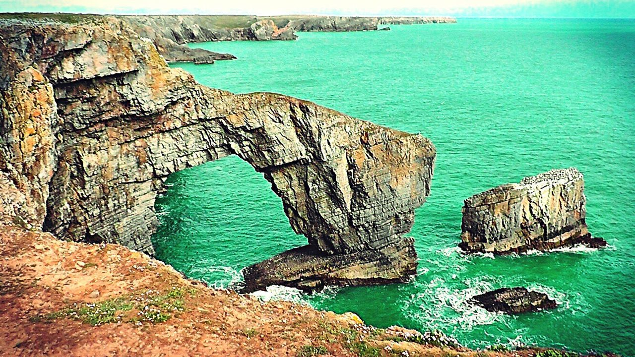 rock - object, sea, rock formation, water, nature, high angle view, geology, scenics, cliff, beauty in nature, physical geography, tranquility, natural arch, no people, day, outdoors, horizon over water, sky
