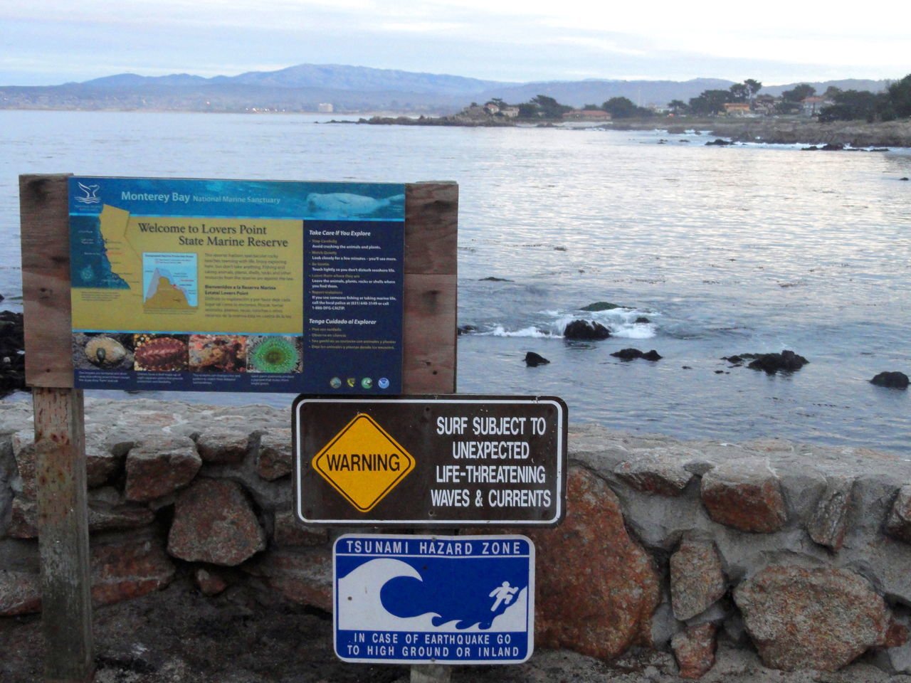 Beach Communication Day Direction Dusk Sky Guidance Information Sign Lovers Point Marine Reserve Mountain Nature Non-western Script Outdoors Rocks On The Beach Sea Shore Signboard Sky Symbol Text Tsunami Hazard Zone Tsunami Sign Water Western Script Yellow