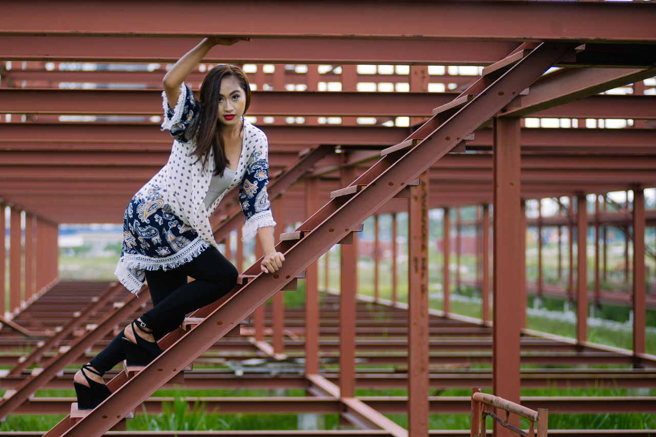 one person, lifestyles, real people, young women, young adult, leisure activity, casual clothing, built structure, full length, standing, architecture, footbridge, day, women, beautiful woman, outdoors