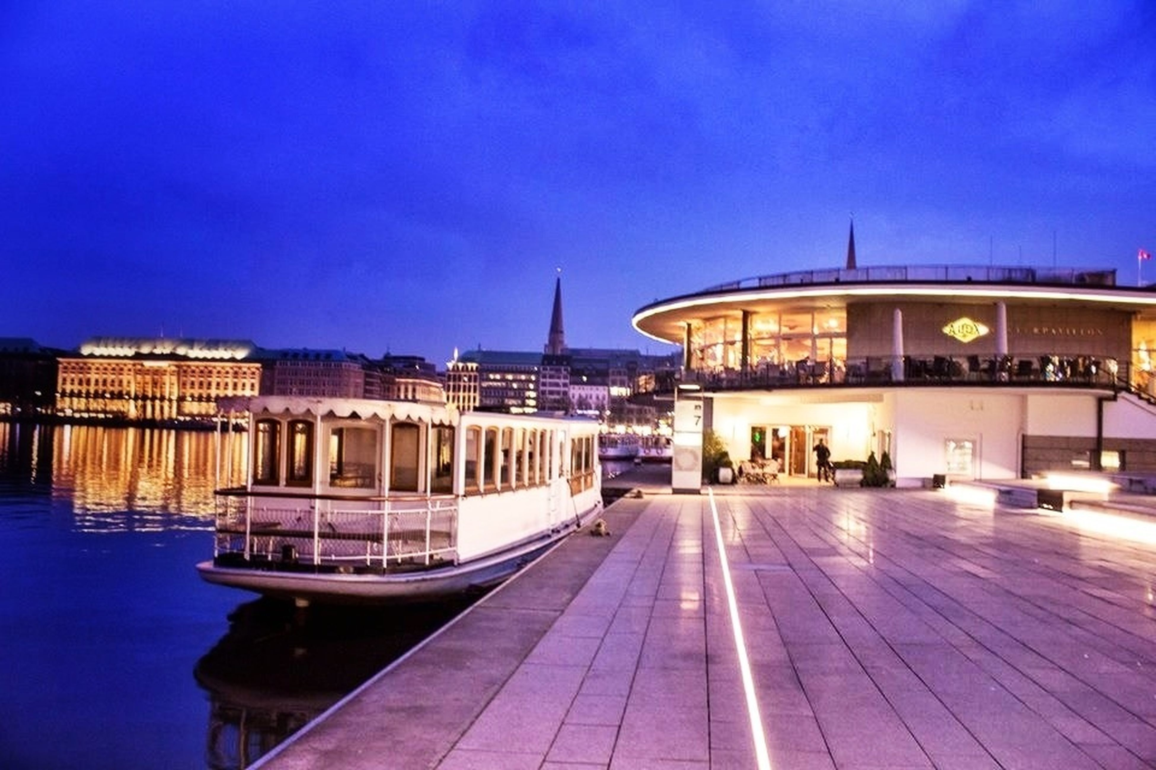 architecture, built structure, blue, building exterior, clear sky, illuminated, copy space, water, transportation, sky, outdoors, night, travel, city, mode of transport, incidental people, travel destinations, railing, nautical vessel, reflection