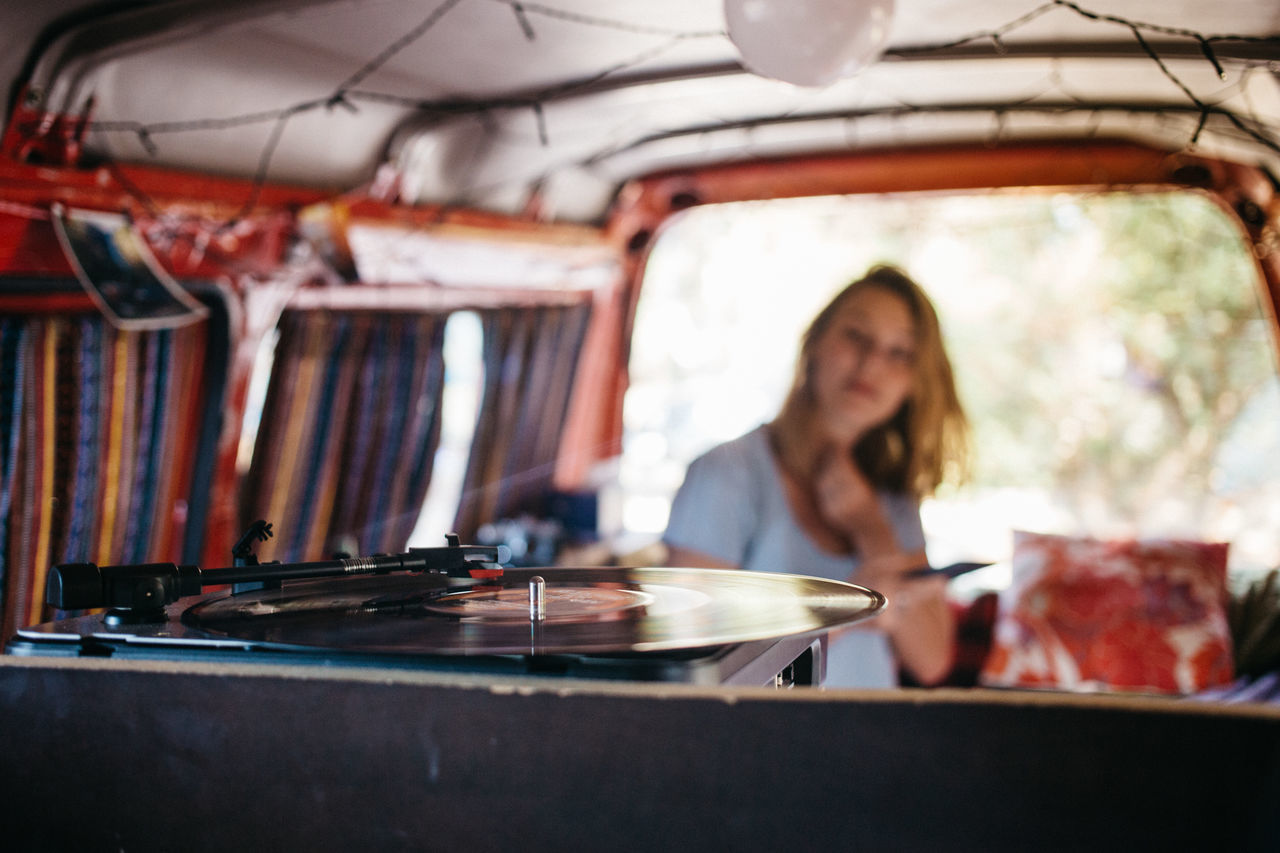 A vinyl record player in a camper van while a woman in the background looks on camper Camping close-up equipment Home Lifestyle metal Music preparation Red technology Turntable vinyl records Woman Market Bestsellers 2017