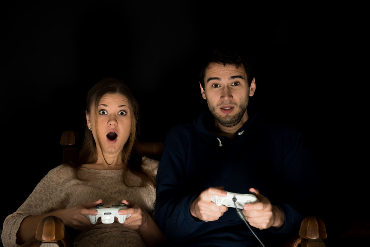 playing games Adult Adults Only Arts Culture And Entertainment Audience Black Background Disbelief Excitement Friendship Gasping Headshot Human Body Part Looking At Camera Men Mouth Open Night Only Men People Portrait Shock Sitting Spectator Togetherness Two People Watching Young Adult