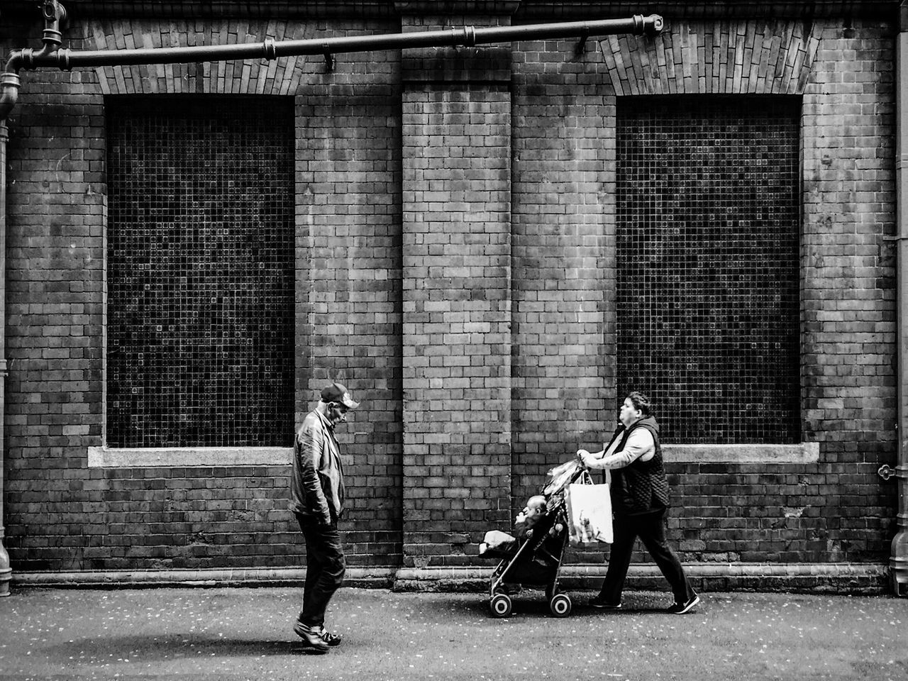 full length, two people, real people, architecture, building exterior, built structure, walking, day, brick wall, outdoors, men, togetherness, lifestyles, childhood, adult, people