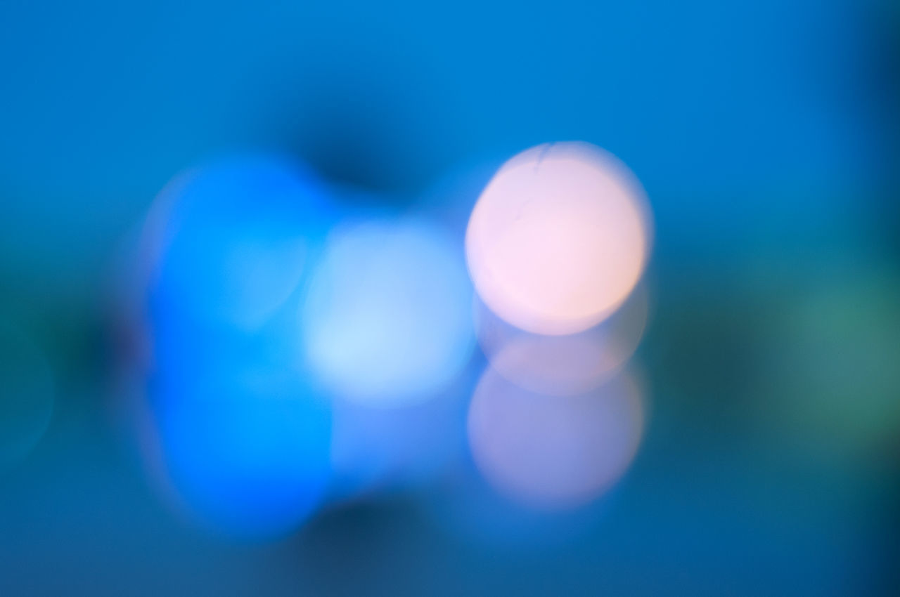 blue, lens flare, defocused, illuminated, close-up, focus on foreground, no people, outdoors, day