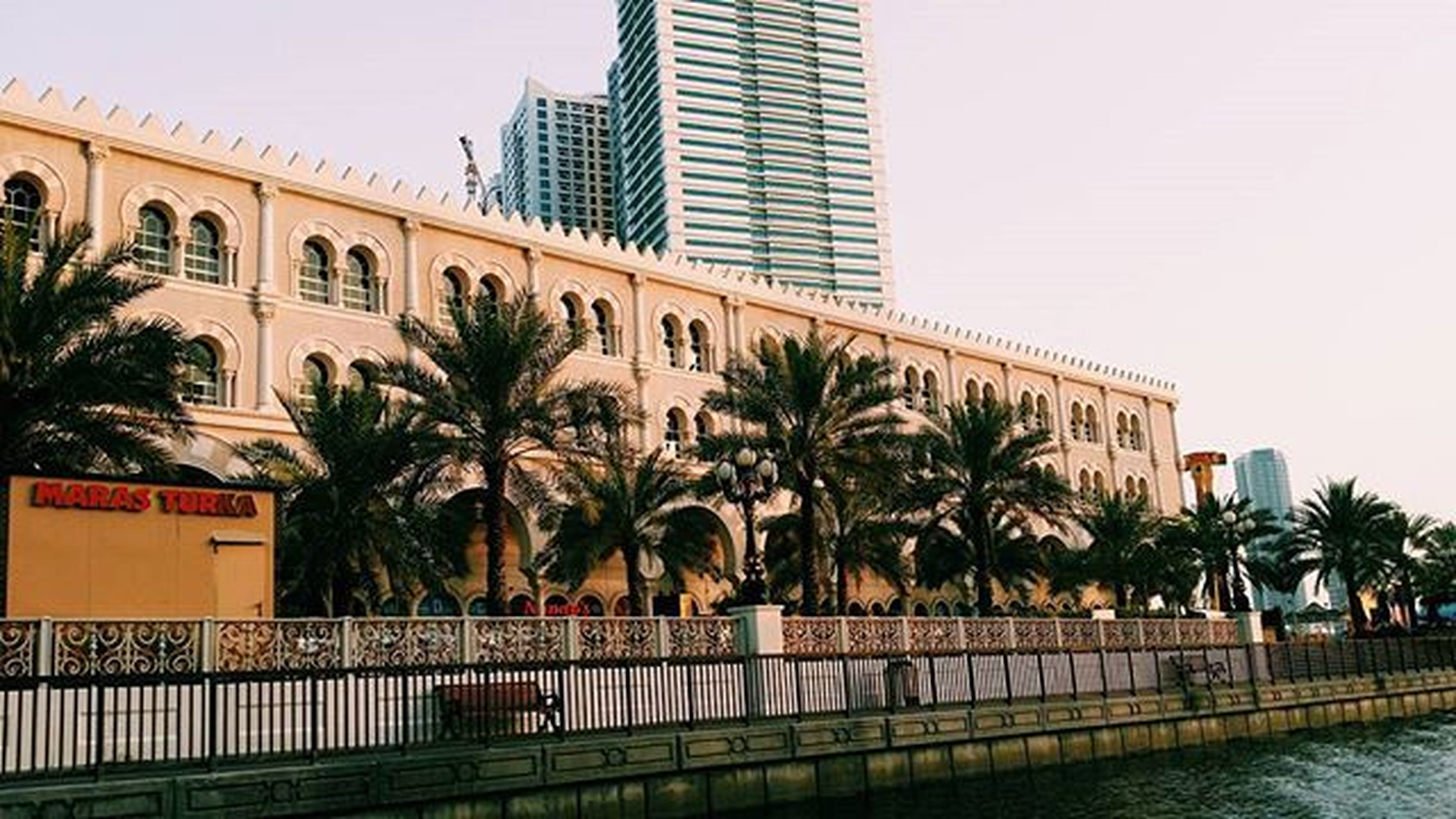 architecture, building exterior, built structure, tree, palm tree, city, clear sky, water, building, sky, office building, residential building, river, tall - high, incidental people, modern, city life, waterfront, outdoors, railing