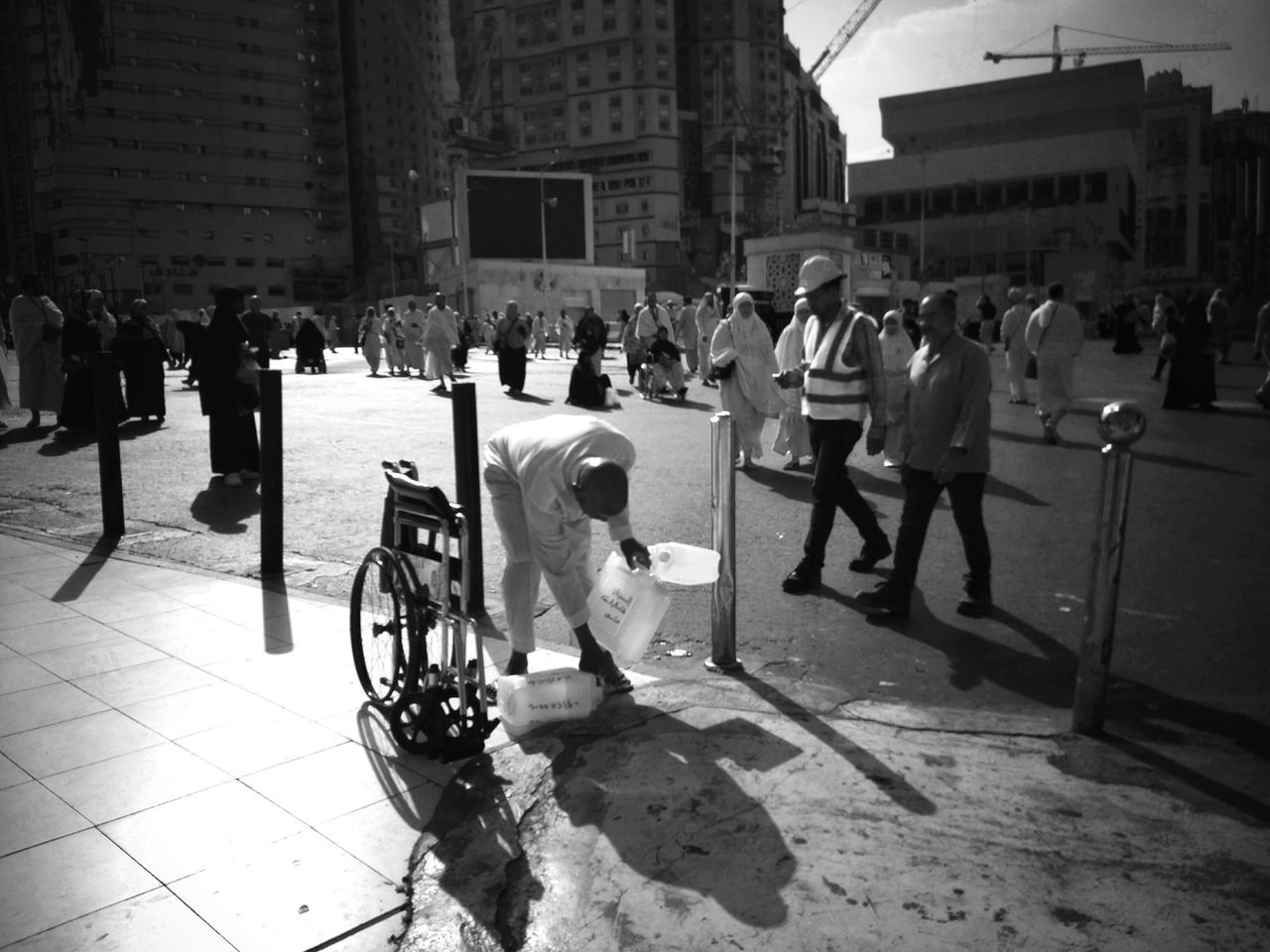 A man collecting bottle on the road of Makkah. Street Photography Alharam Mecca Saudi Arabia Outdoors Catch The Moment MeccaStreet Traveling The World Travel Destinations Crowd Xiaomimi5 Travelphotography Journey Of Life People On The Street Mobilephotography Black And White Photography Journey Of Souls Makkah Al Mukaramah