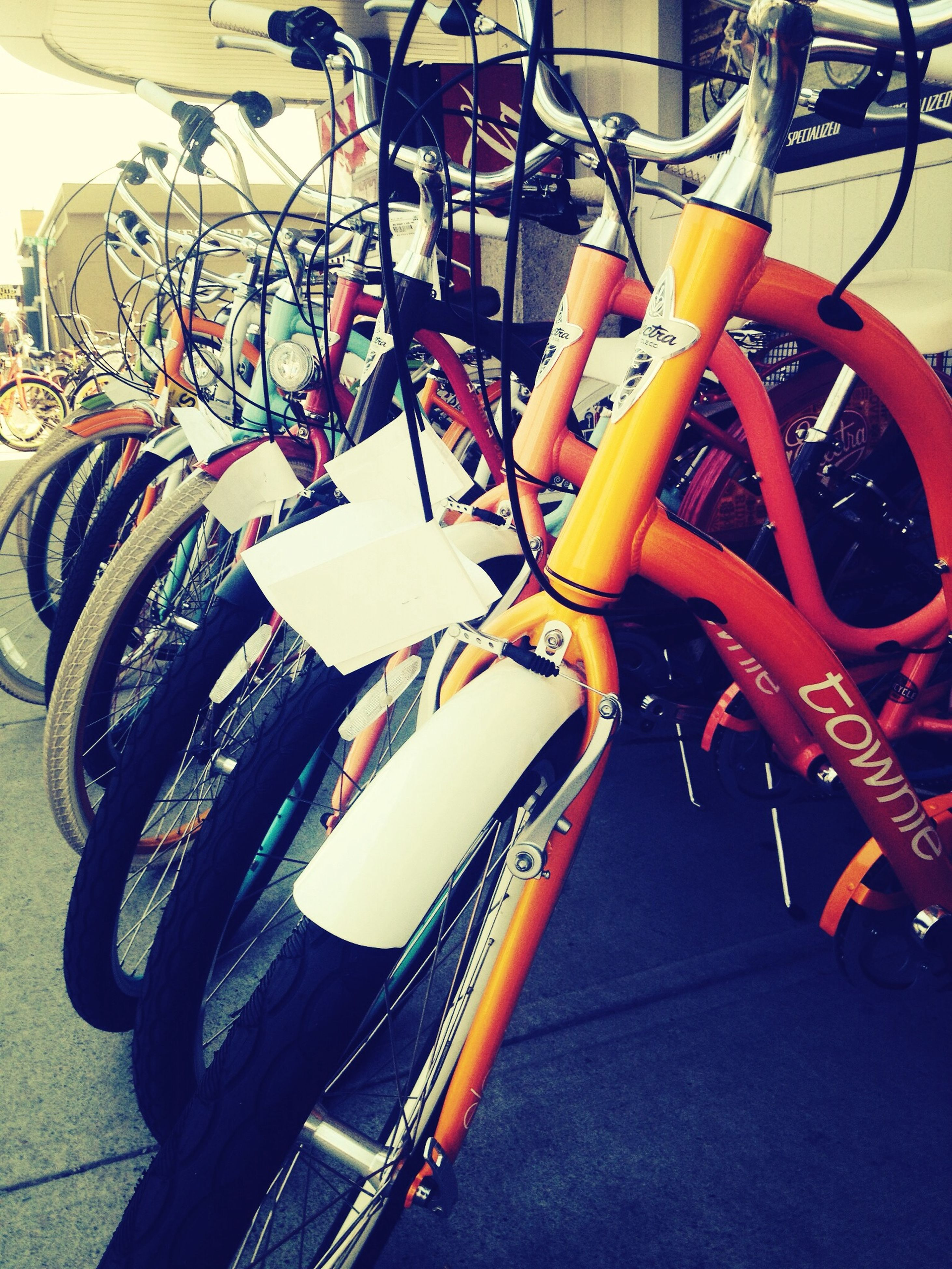 bicycle, metal, no people, land vehicle, close-up, outdoors, day, parking, hanging, transportation, sunlight, low angle view, arts culture and entertainment, decoration, street, stationary, built structure, mode of transport, red, city