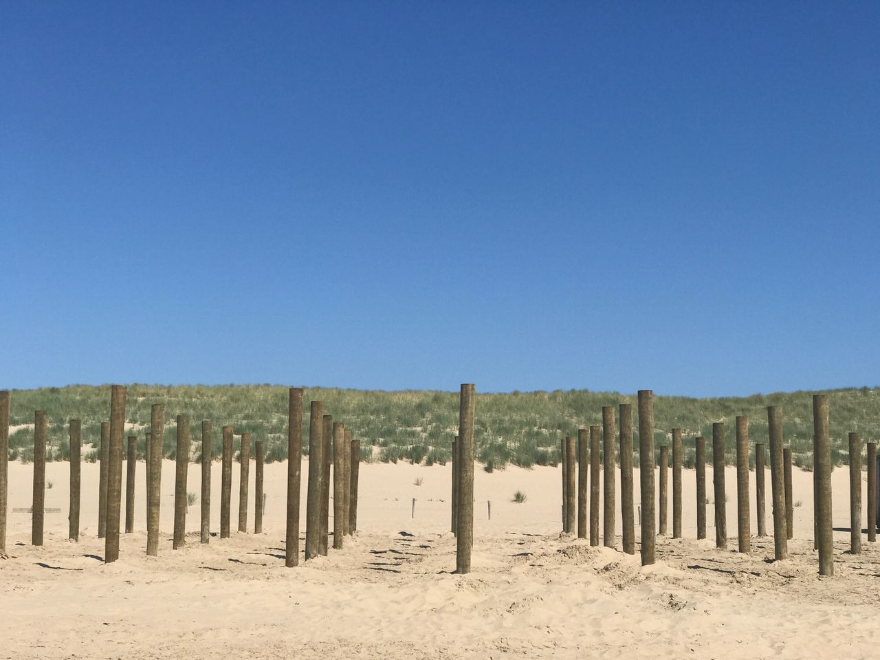 Wooden Posts On Field Against Clear Blue Sky