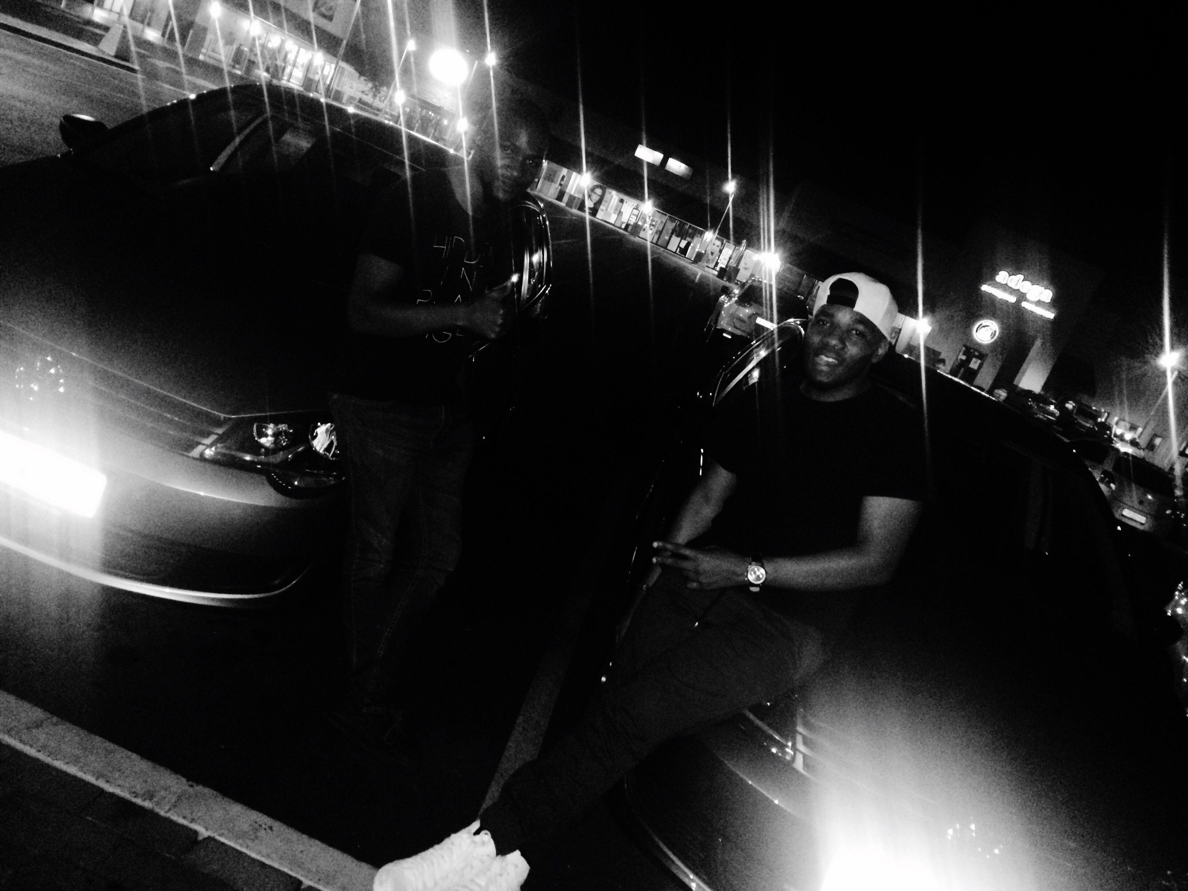 night, illuminated, land vehicle, transportation, mode of transport, men, lighting equipment, car, street light, lifestyles, street, leisure activity, city, arts culture and entertainment, light - natural phenomenon, city life, light beam, incidental people, building exterior