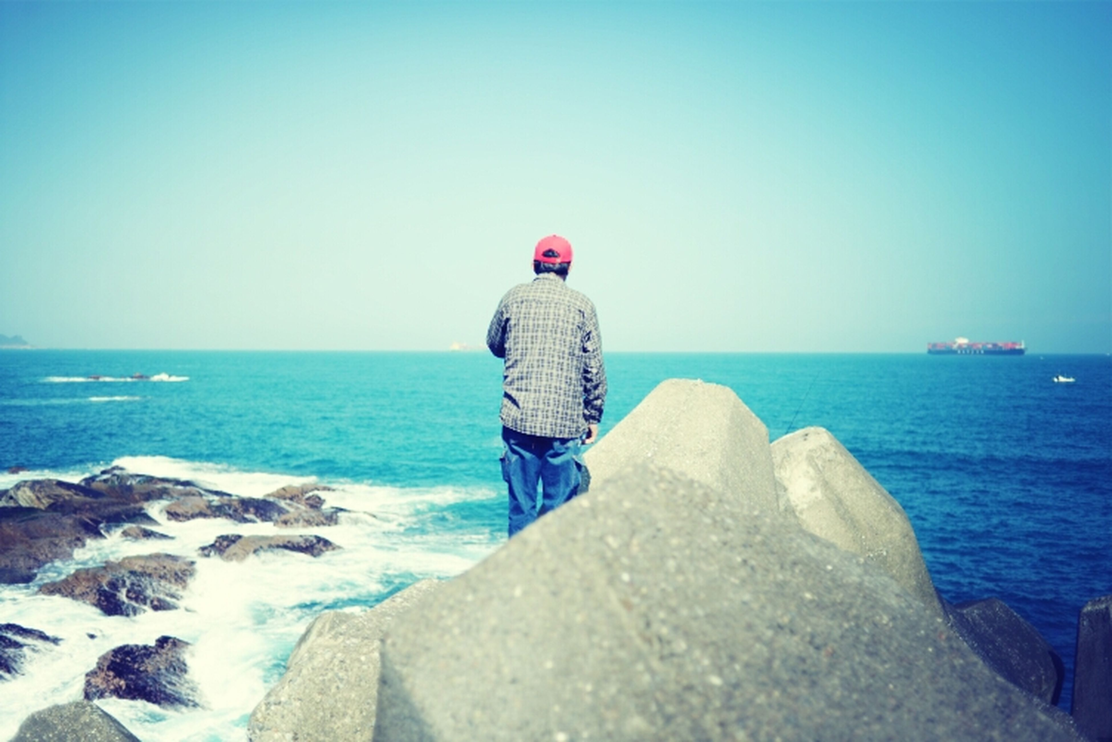 sea, horizon over water, water, rear view, clear sky, lifestyles, leisure activity, full length, standing, copy space, blue, rock - object, casual clothing, scenics, beach, tranquil scene, tranquility, beauty in nature
