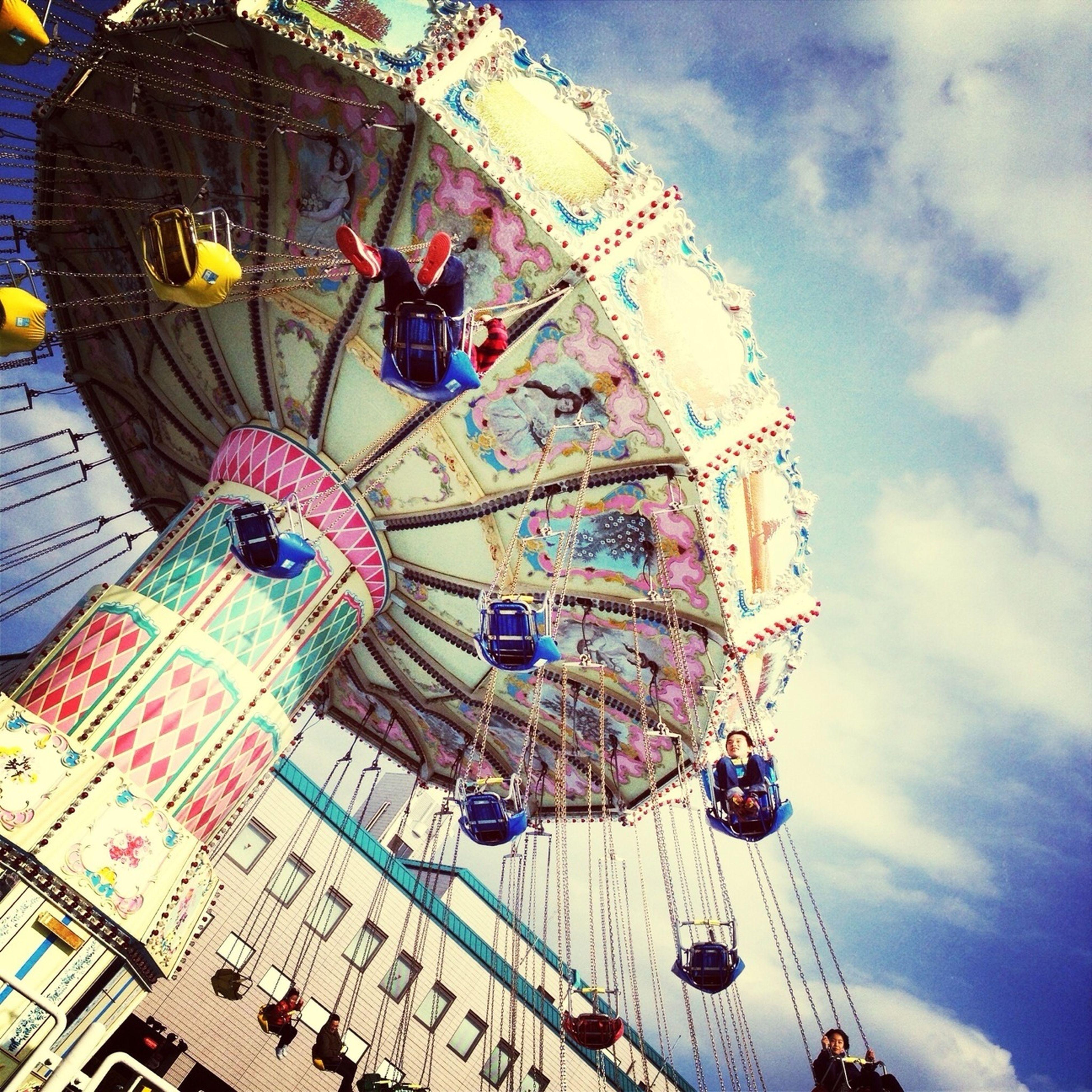 amusement park, amusement park ride, ferris wheel, arts culture and entertainment, low angle view, sky, cloud - sky, built structure, architecture, fun, travel, multi colored, day, transportation, outdoors, chain swing ride, tourism, travel destinations, incidental people, cloudy