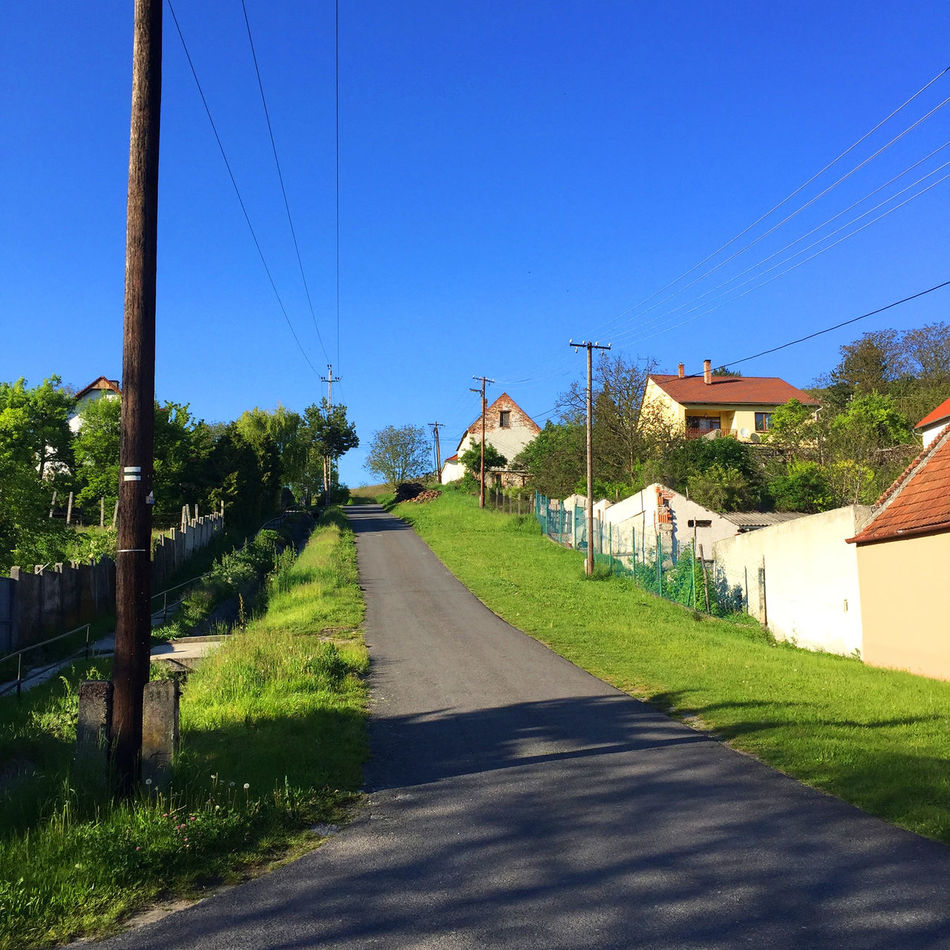 Architecture Blue Cable Clear Sky Day Diminishing Perspective Grass Long Narrow No People Outdoors Plant Power Line  Road Road Sky Steep Sunlight Sunny The Way Forward Tree Vanishing Point Village Walkway
