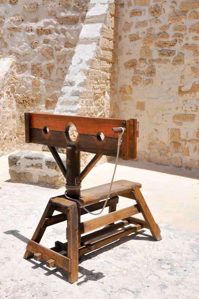 Punishment stocks on display in outdoor courtyard at the historic tourist attraction the Round House in Fremantle, Western Australia. Brick Building Carpentry Courtyard  Crime Display Framework Fremantle, Western Australia Gaol Historic Holes Humiliation Limestone Old Outdoors Pillory Prison Public Humiliation Punishment Stocks Stone The Round House Tourist Attraction  Wall Wooden