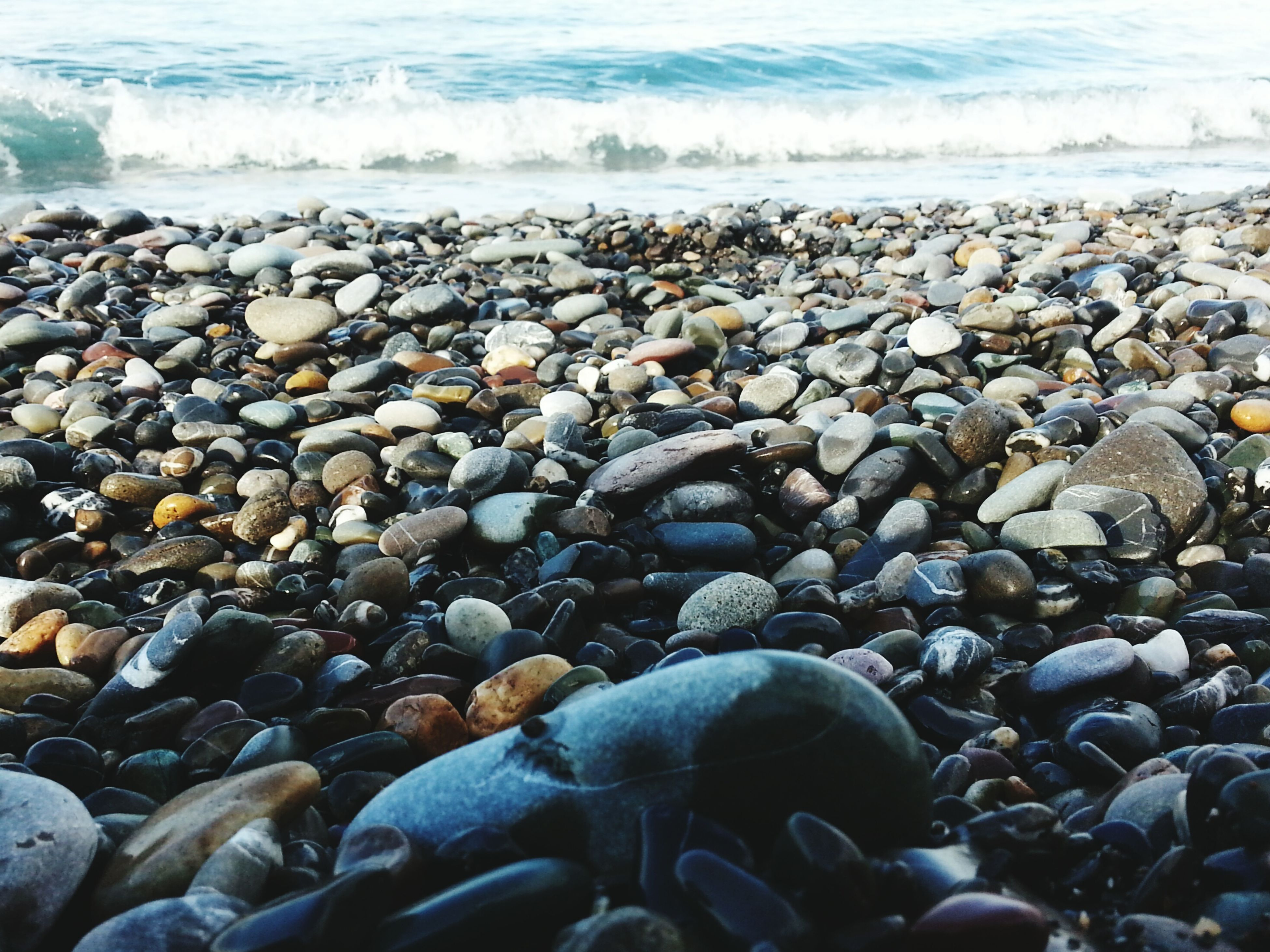 beach, sea, pebble, shore, water, stone - object, rock - object, nature, abundance, tranquility, large group of objects, sand, stone, wave, beauty in nature, horizon over water, scenics, tranquil scene, surf, surface level