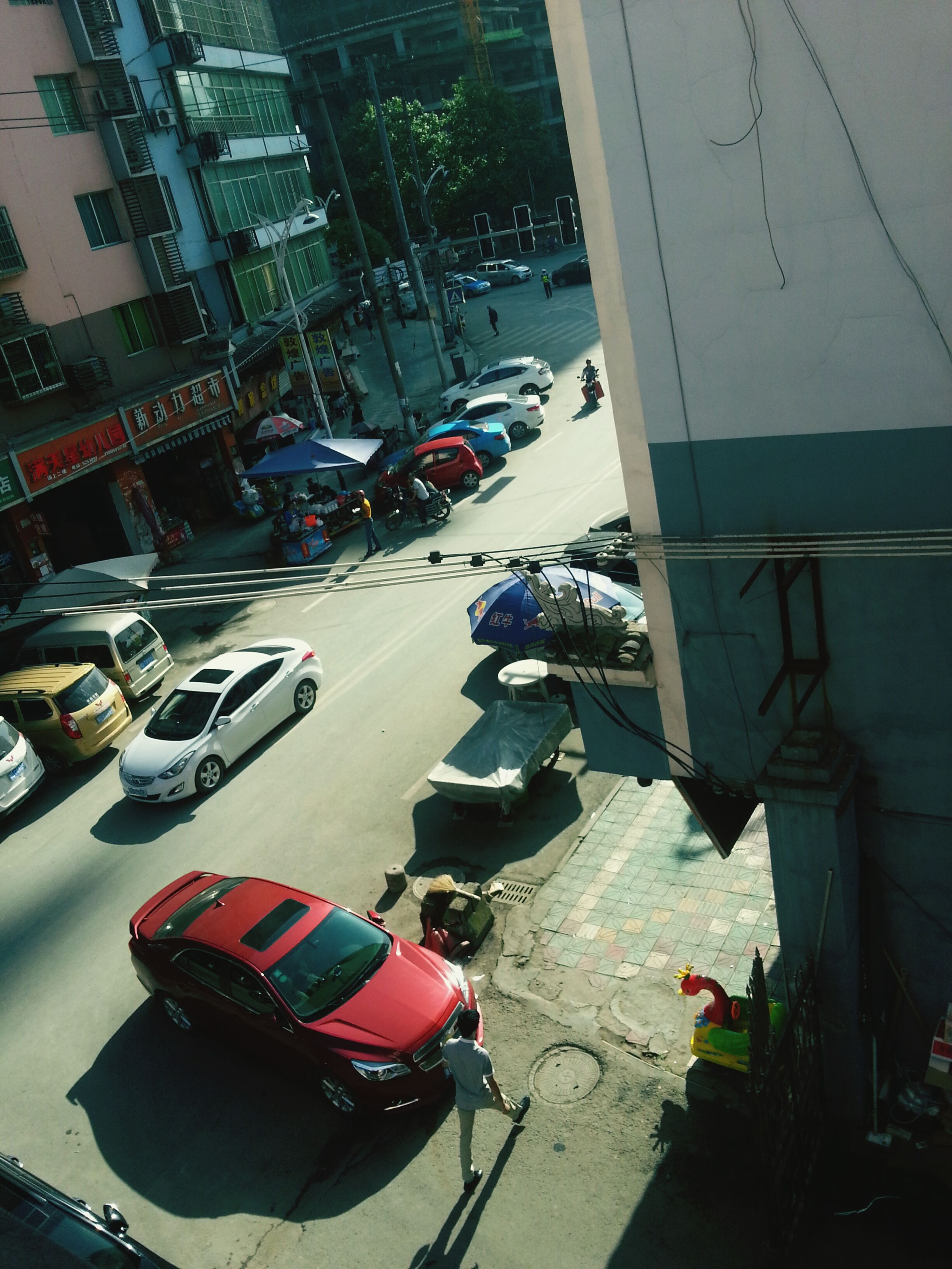 car, transportation, mode of transport, land vehicle, street, building exterior, city, high angle view, architecture, built structure, road, parking, city life, city street, incidental people, traffic, stationary, outdoors, day, parking lot