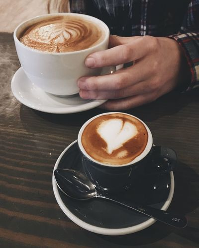 EyeEm Selects Coffee - Drink Coffee Cup Drink Frothy Drink Refreshment Cappuccino Saucer Froth Art Food And Drink Human Hand Latte Table Human Body Part One Person Cafe Holding Real People Froth Indoors  Beverage