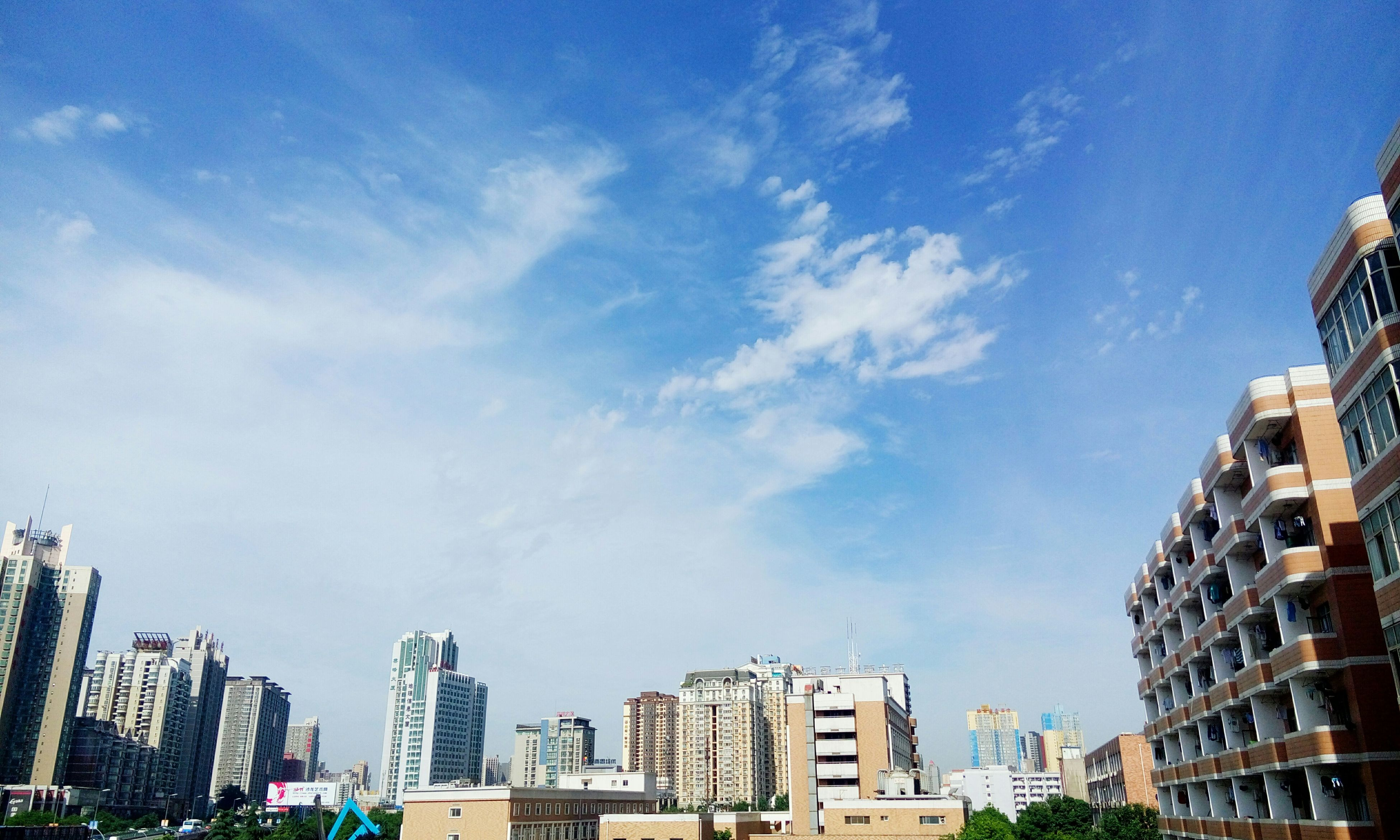 building exterior, architecture, built structure, city, low angle view, skyscraper, sky, modern, tall - high, residential building, office building, building, cityscape, residential structure, tower, blue, city life, residential district, cloud - sky, day
