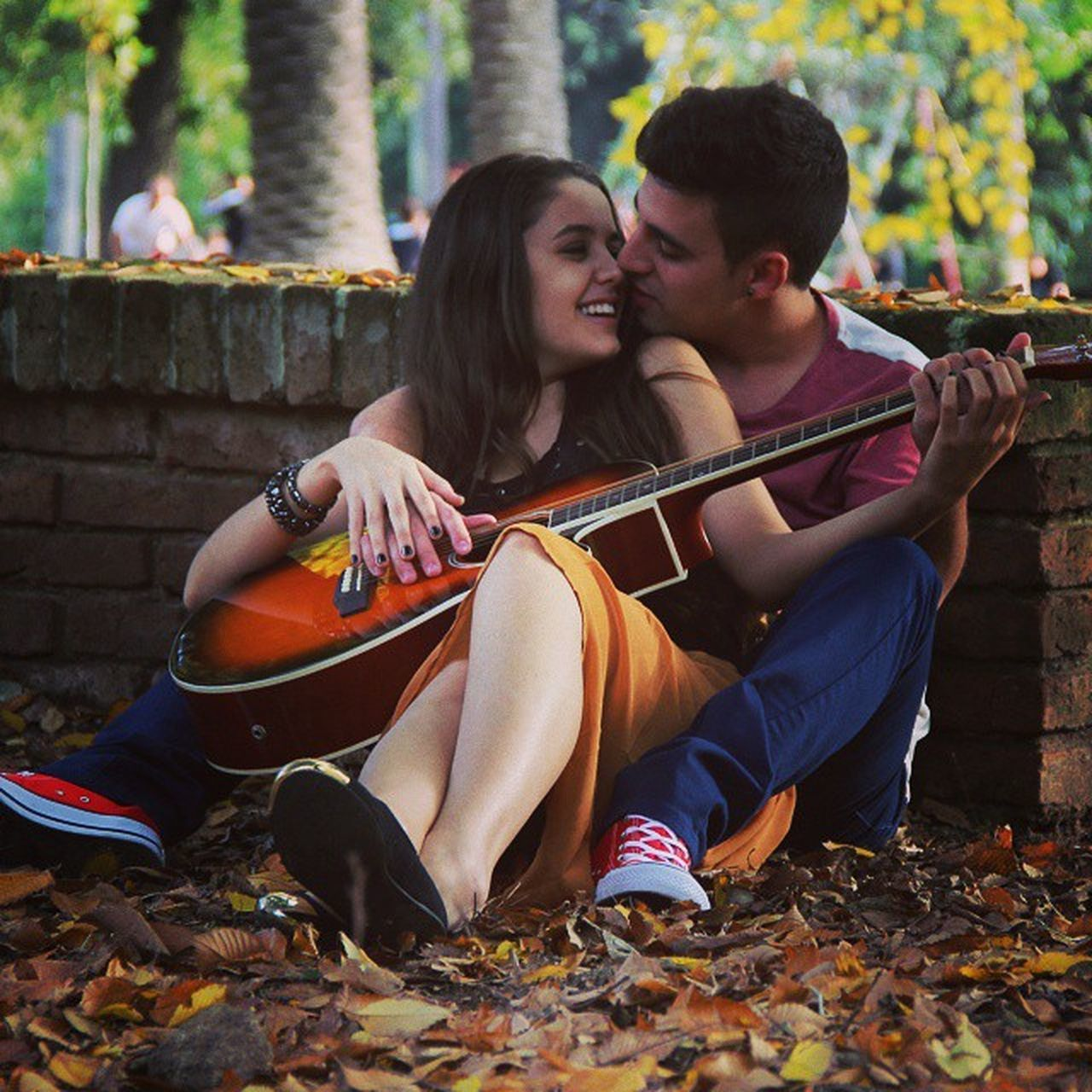 two people, autumn, leaf, music, heterosexual couple, togetherness, playing, love, young women, couple - relationship, smiling, young adult, change, arts culture and entertainment, adult, men, leisure activity, cheerful, young couple, outdoors, guitar, bonding, young men, happiness, full length, people, musician, lifestyles, plucking an instrument, day, sitting, adults only, nature, musical instrument, women, tree
