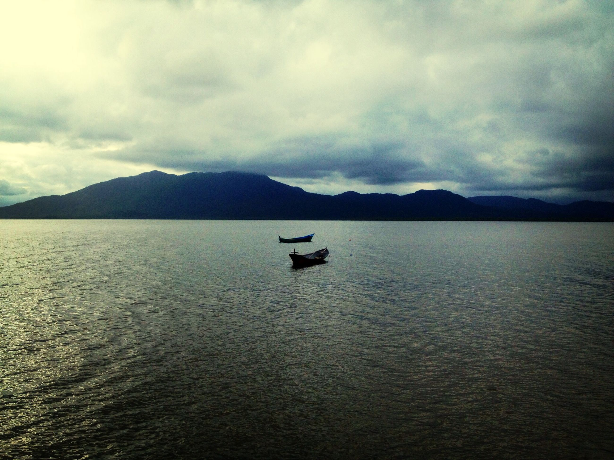 water, nautical vessel, transportation, sky, boat, mode of transport, tranquil scene, waterfront, mountain, tranquility, cloud - sky, scenics, beauty in nature, cloudy, sea, nature, cloud, lake, mountain range, rippled