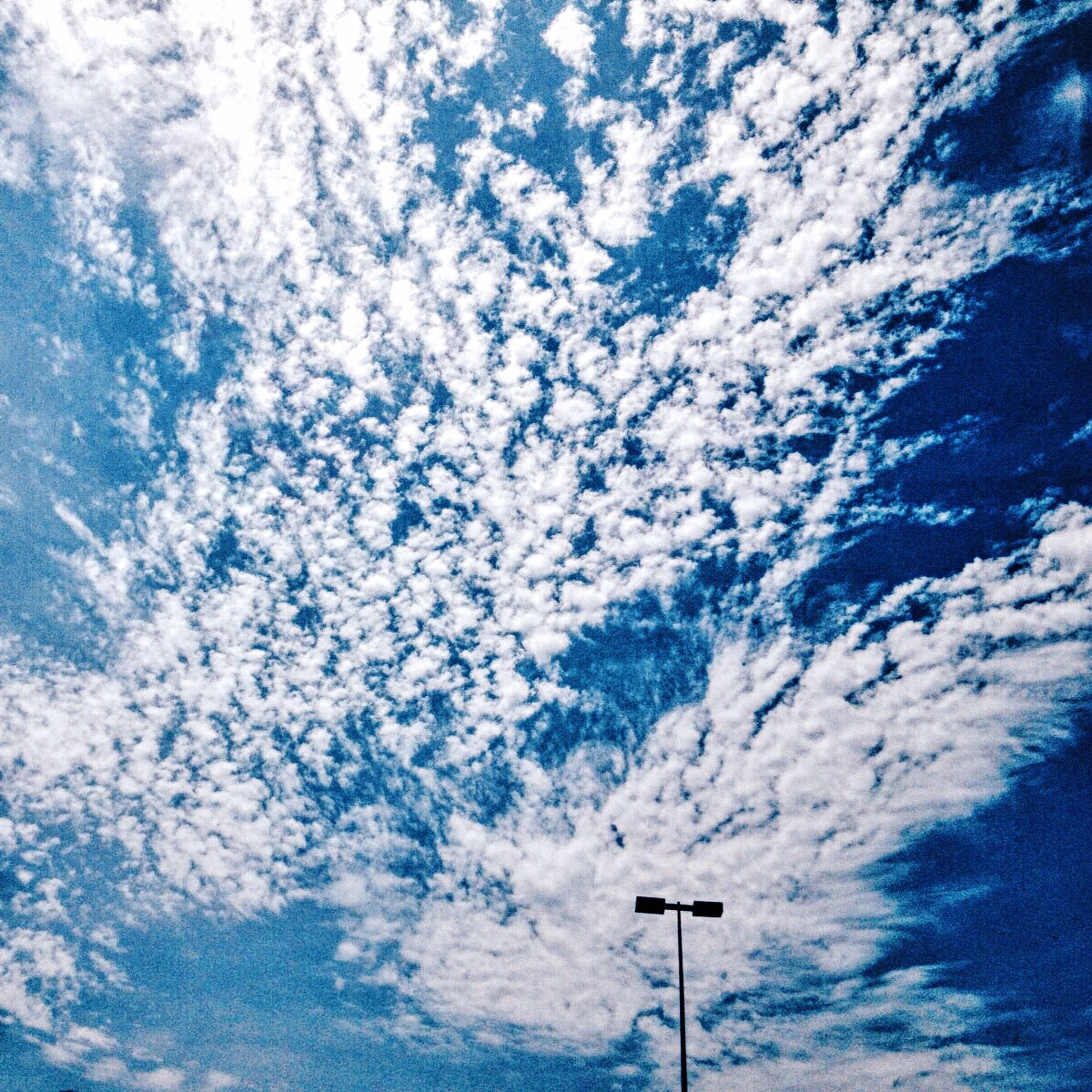 low angle view, sky, cloud - sky, blue, street light, cloudy, cloud, tranquility, nature, beauty in nature, scenics, high section, outdoors, day, no people, lighting equipment, pole, cloudscape, weather, tranquil scene