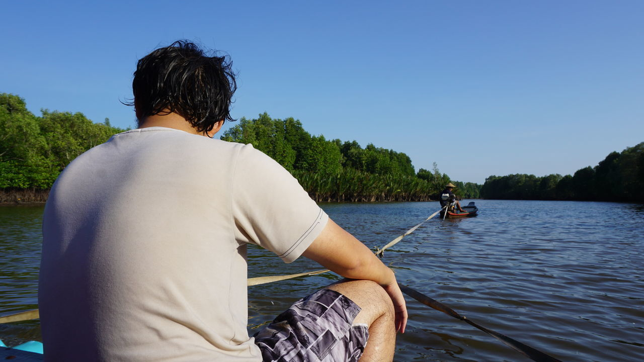 real people, rear view, one person, water, leisure activity, men, river, clear sky, sitting, nautical vessel, outdoors, day, lifestyles, transportation, nature, casual clothing, standing, tree, sailing, beauty in nature, sky, adult, people