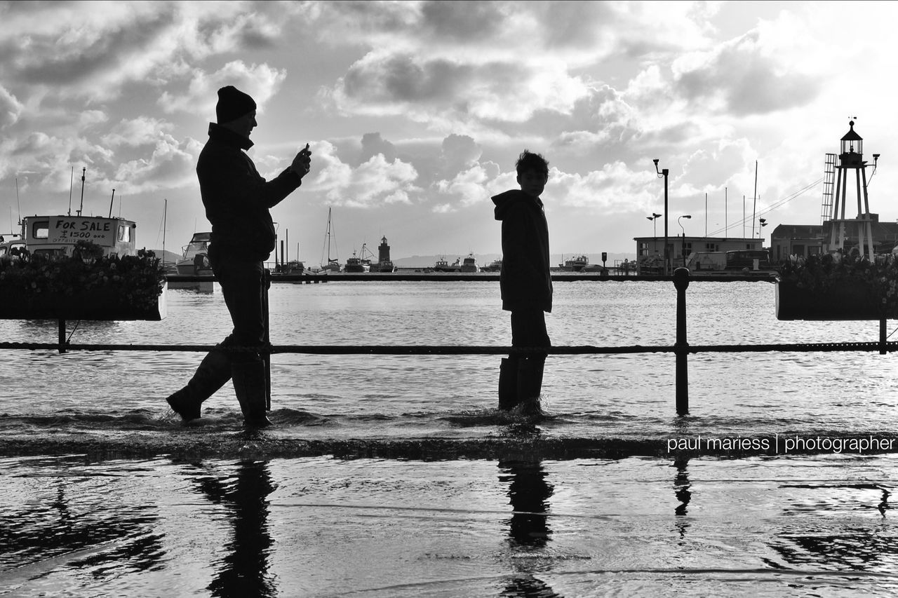 water, real people, sky, men, waterfront, two people, silhouette, standing, cloud - sky, full length, sea, leisure activity, outdoors, lifestyles, nature, nautical vessel, day, beauty in nature, people