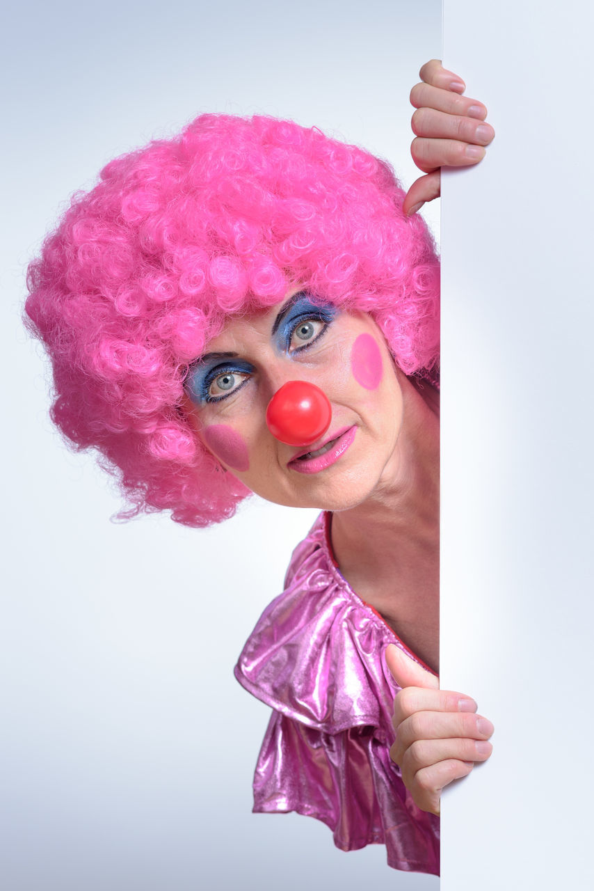 Portrait Of Clown Holding Placard Against White Background