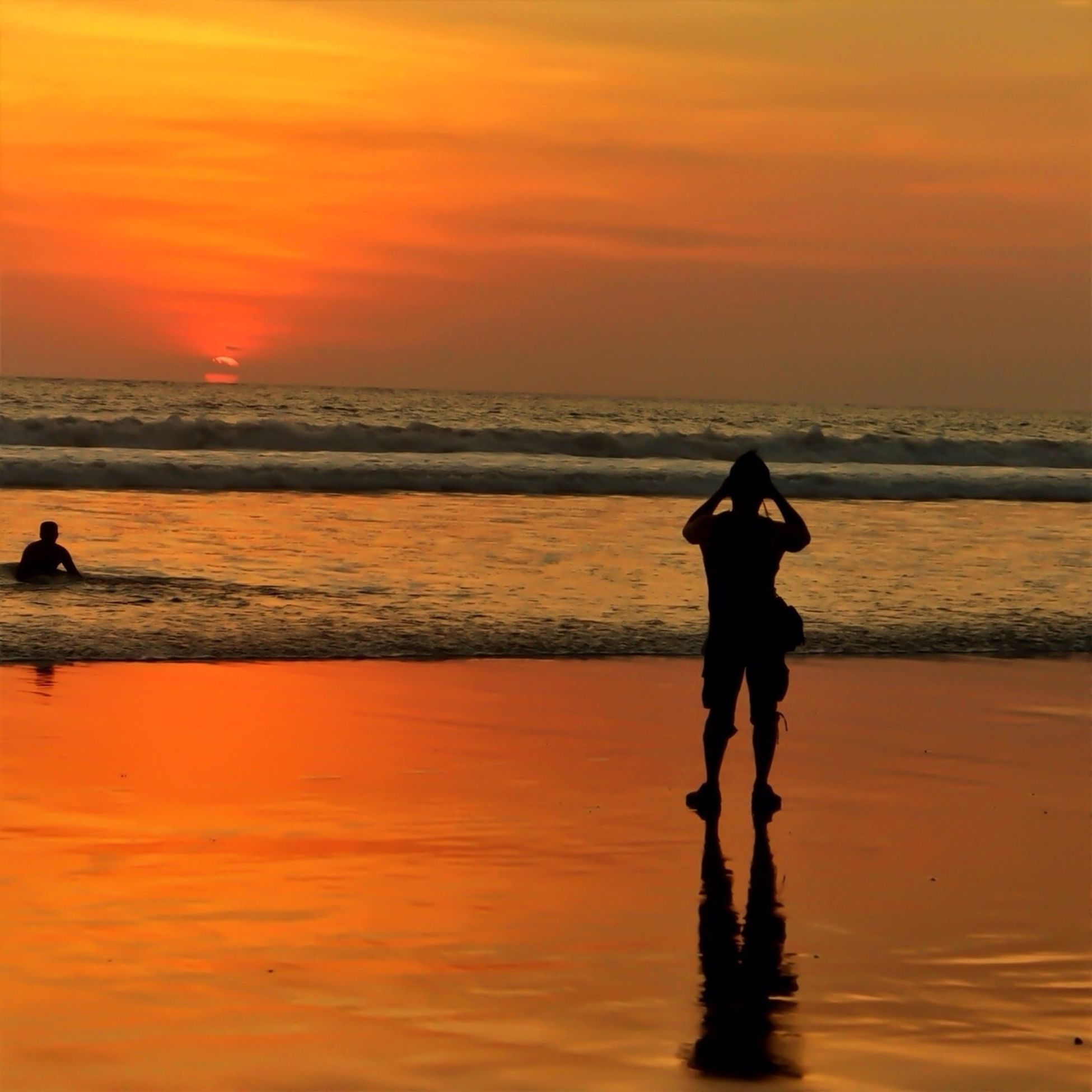 sunset, sea, horizon over water, silhouette, water, orange color, beach, sky, scenics, leisure activity, lifestyles, beauty in nature, shore, standing, tranquil scene, tranquility, idyllic, men, vacations