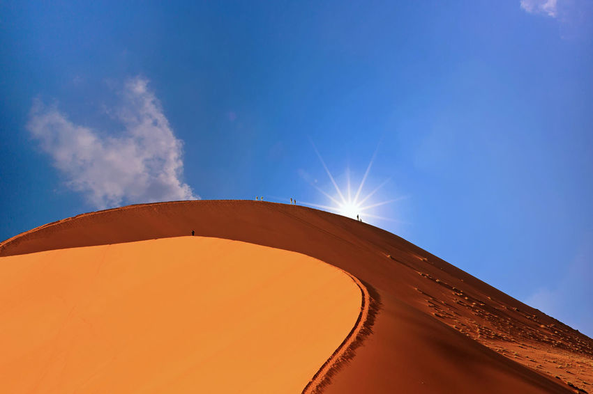 Snad dune in Namib Naukluft desert with people climbing, with the sun peeping over the top - Namibia , Southern Africa Beauty In Nature Blue Blue Sky And Clouds Climbing Day Dunes Hiking Hot Low Angle View Namib Desert Namib Naukluft National Park Namibia Namibia Landscape Nature Outdoors Sand Sand Dune Sesriem, Namibia Sky Sossusvlei Southern Africa Sunlight Sweltering Temperature Connected By Travel