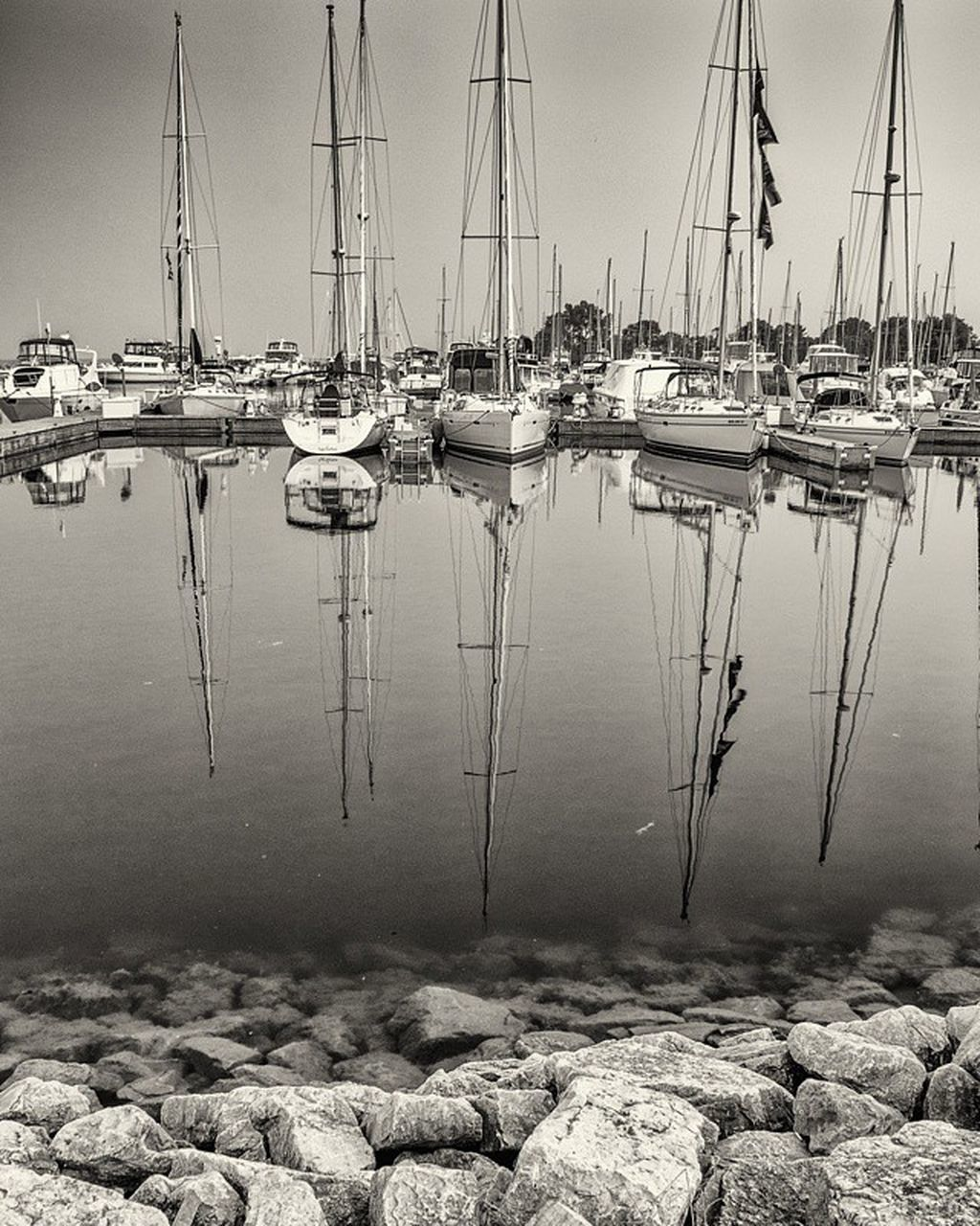 moored, reflection, nautical vessel, outdoors, water, harbor, no people, mode of transport, day, mast, transportation, large group of objects, nature, travel destinations, sailboat, architecture, sky, yacht