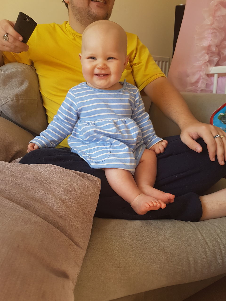 Smiling Baby Girl Sitting On Father Lap At Home