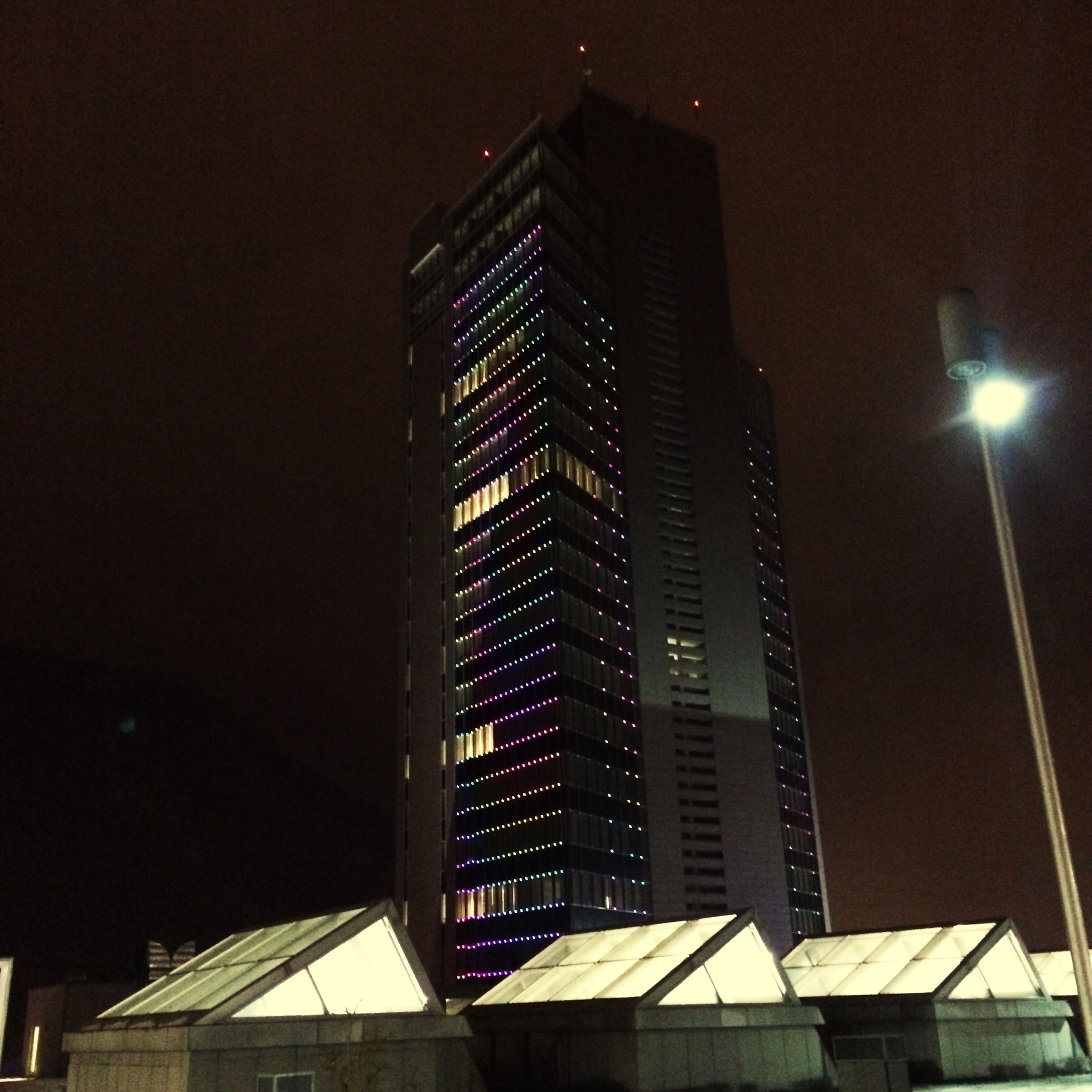 building exterior, architecture, built structure, city, skyscraper, low angle view, illuminated, night, modern, office building, tall - high, tower, building, clear sky, residential building, city life, tall, sky, residential structure, outdoors