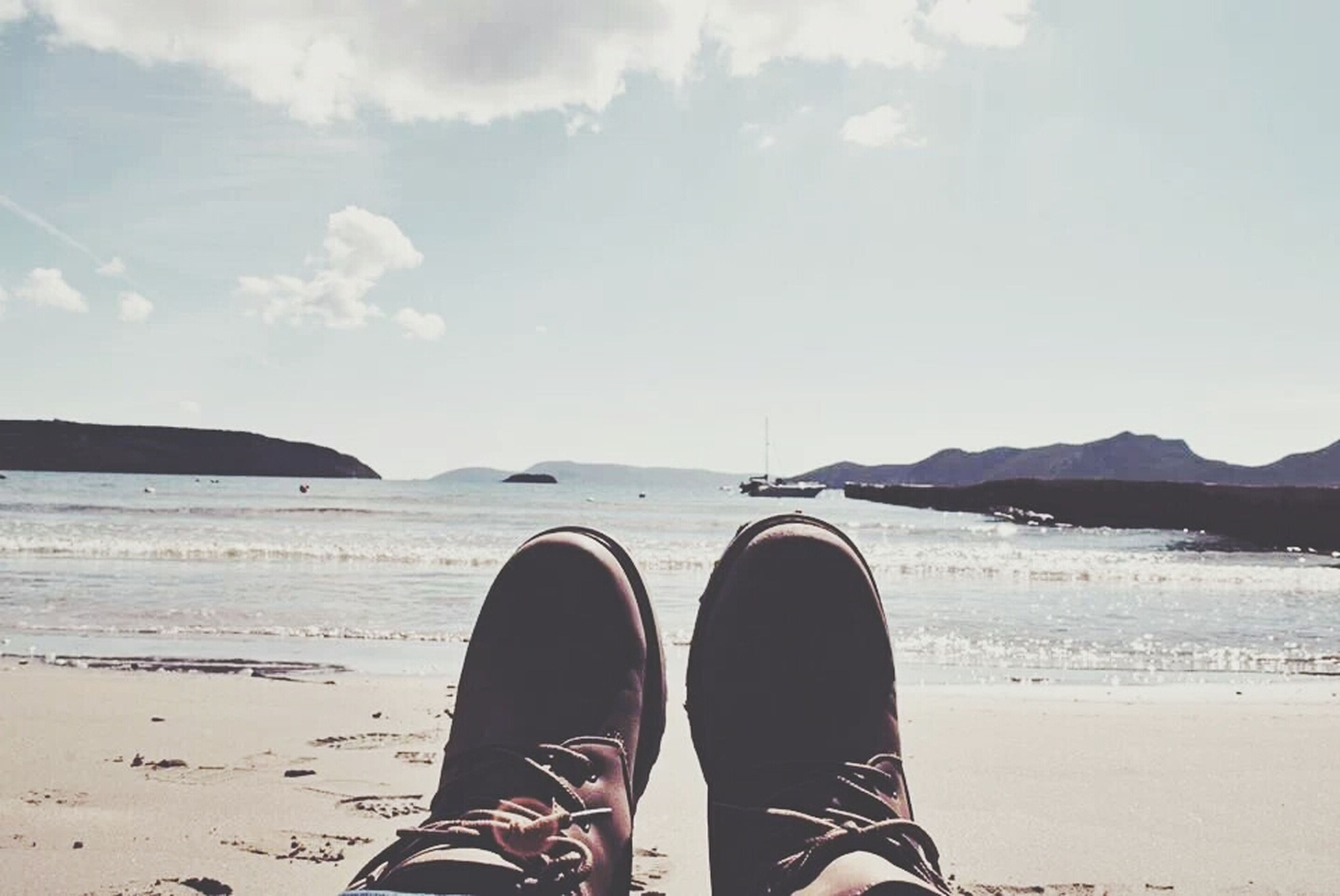 low section, person, personal perspective, beach, shoe, water, sand, lifestyles, shore, human foot, sea, leisure activity, standing, footwear, sky, men, tranquil scene